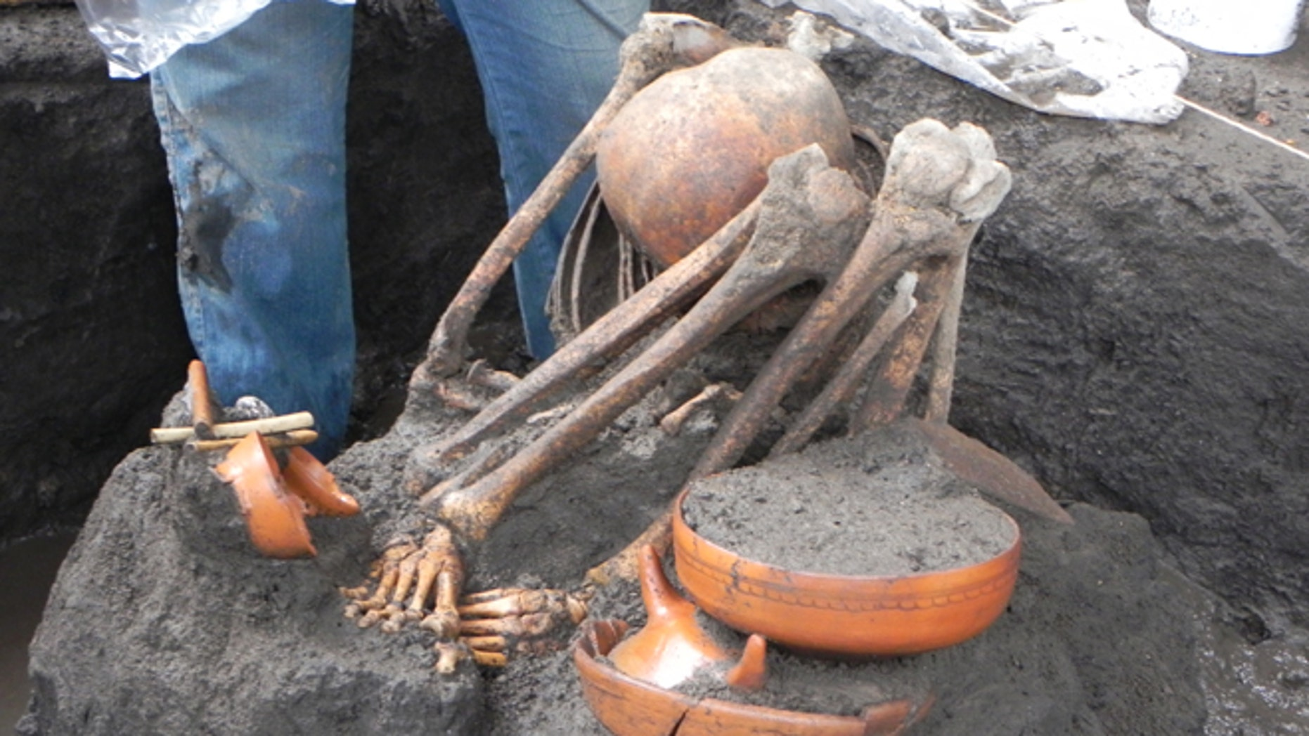 A human skeleton lies next to an offering found during the excavations for the newest subway line in Mexico City.