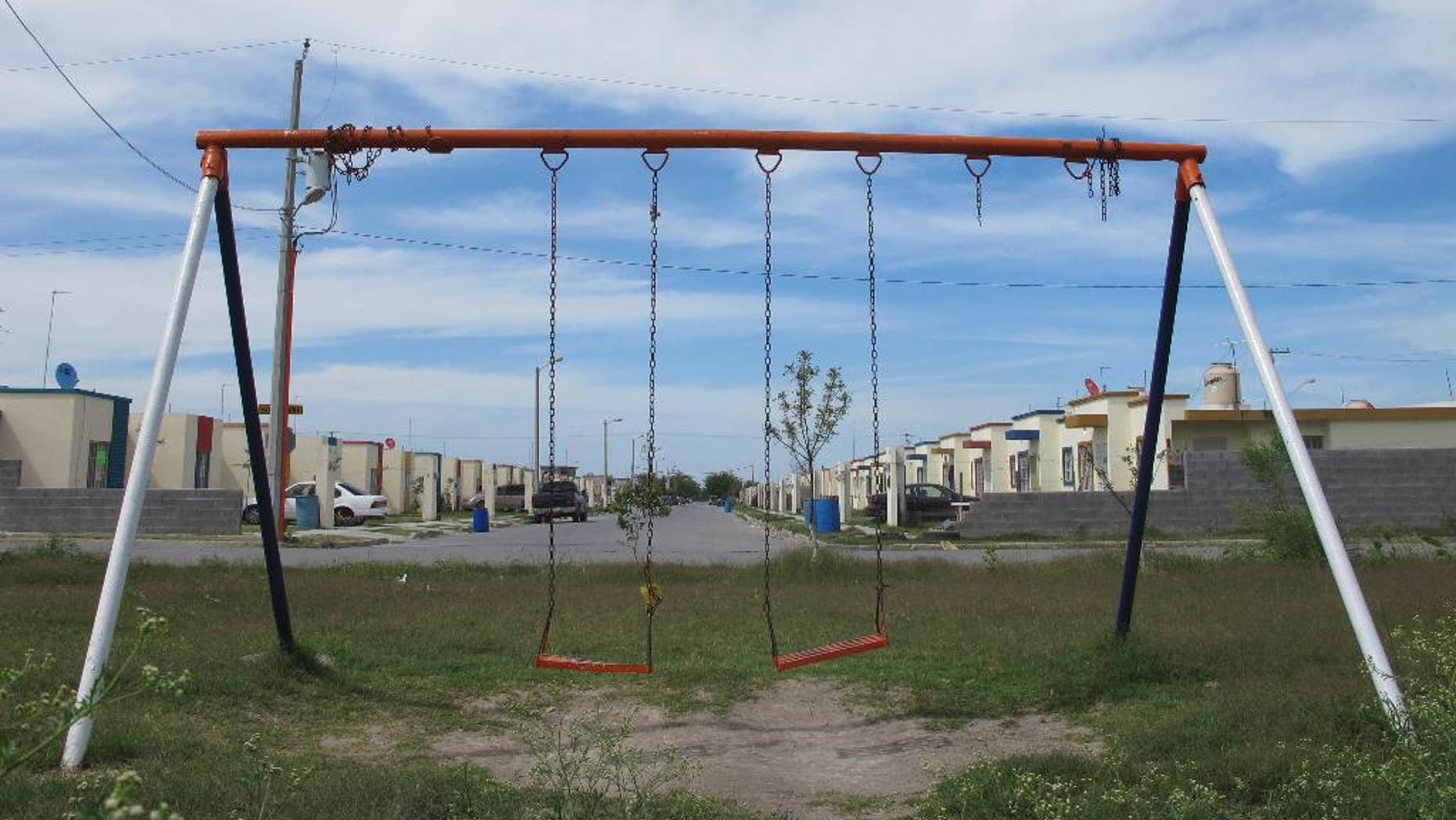 In this April 9, 2014 photo, a playground stands empty in the San Pedro subdivision on the outskirts of Matamoros, in Mexico's state of Tamaulipas. Of four women interviewed in this working-class neighborhood, none would give their names. One said her husband was taken by gunmen 2 ½ years ago. Another said it had been three years since her 28-year-old son disappeared. Yet another recounted when a marine helicopter opened fire from the air, sending residents scrambling for cover. (AP Photo/Christopher Sherman)