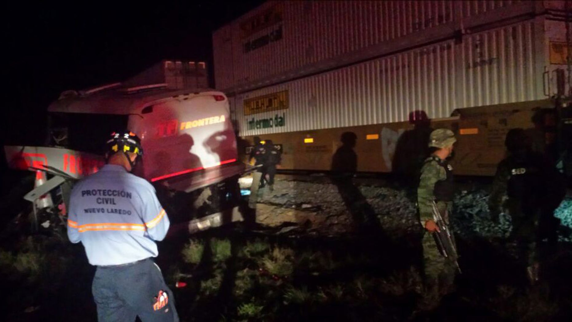 Army soldiers and civil protection workers on the scene of an accident where a passenger bus and a freight train collided at a grade crossing, in Anahuac, Mexico, Friday, Feb. 13, 2015. According to Mexican sources at least 16 people are dead and dozens injured. (AP Photo/El Mañana de Nuevo Laredo)