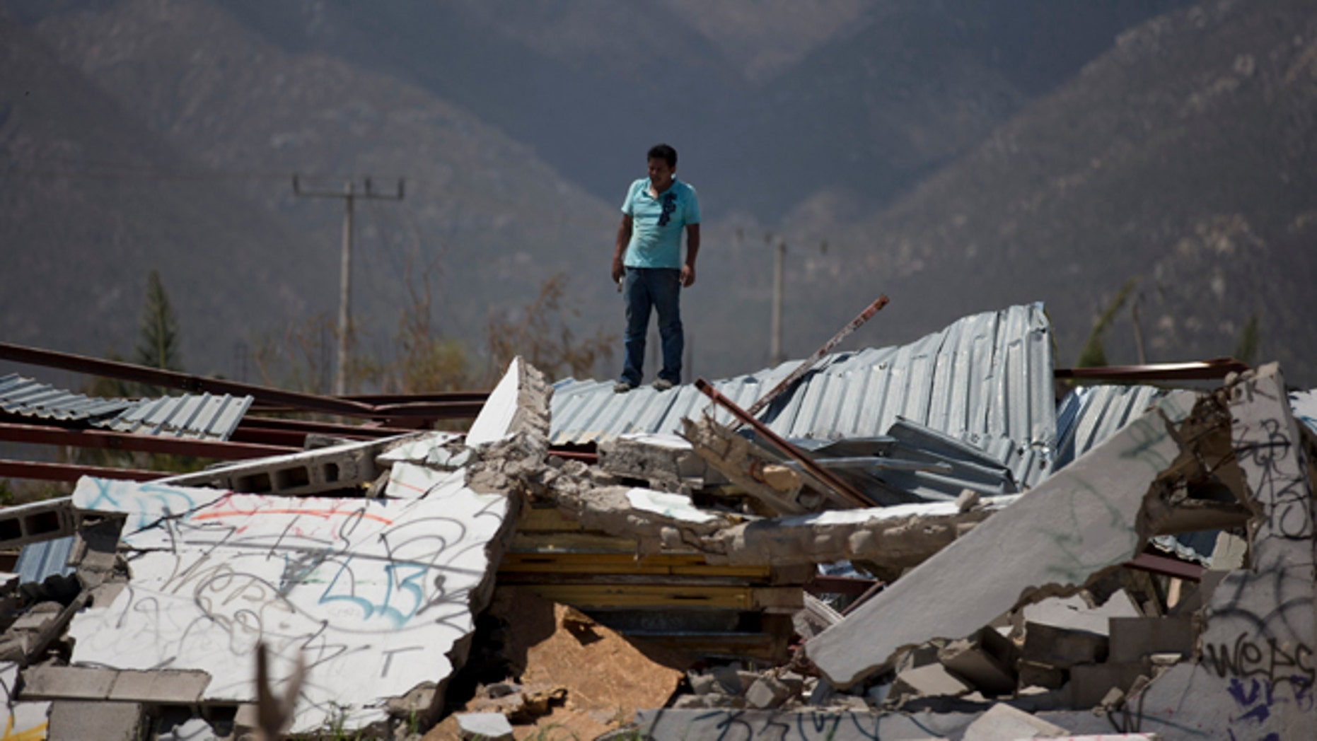 A man stands on top of a collapsed warehouse, looking for building material to salvage after Hurricane Odile destroyed his home in San Jose de los Cabos, Mexico, Thursday, Sept. 18, 2014. Water and electricity service remained out and phone service was intermittent. Odile struck late Sunday as a Category 3 storm. (AP Photo/Dario Lopez-Mills)