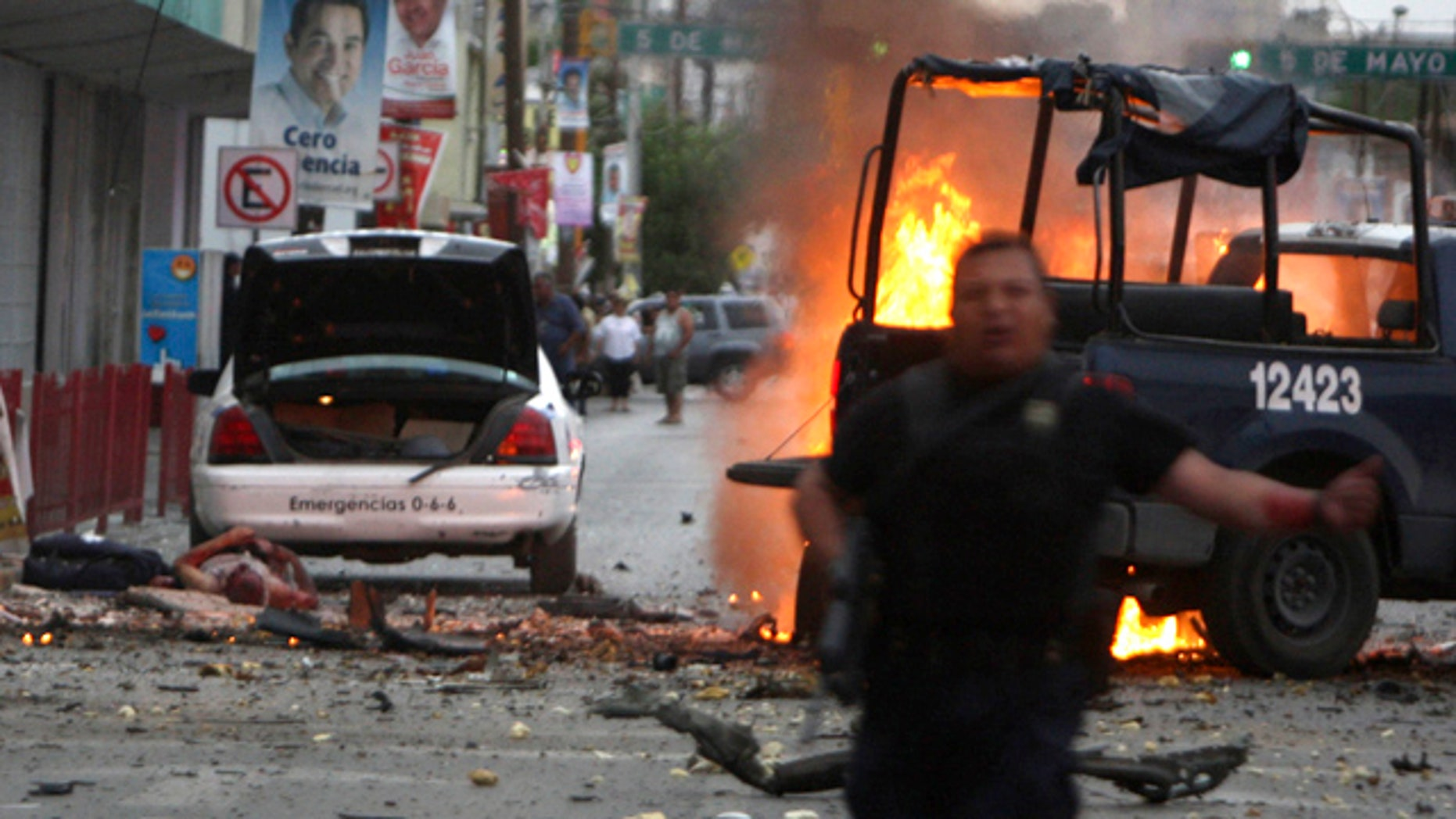 July 15, 2010: A police officer runs after an attack on police patrol trucks that killed two officers in the border city of Ciudad Juarez, Mexico.