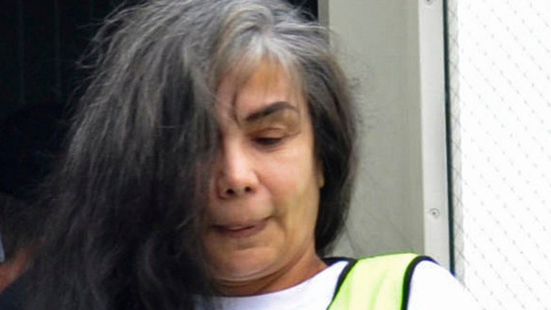FILE - In this Aug. 20, 2013, file photo, provided by Mexico's Interior Department shows Sandra Avila Beltran in handcuffs as she is escorted by federal authorities upon arrival to Benito Juarez airport in Mexico City. A Mexican federal judge has thrown out a five-year, money-laundering sentence against Avila, ordering the immediate release of the so-called Queen of the Pacific for her alleged role as a liaison between Mexican and Colombian cartels. A statement issued Saturday Feb. 7, 2015, by the Attorney Generals Office says the judge ruled that Avila had already been tried for the same crime in Mexico and the United States. (AP Photo/Mexico Interior Department, File)