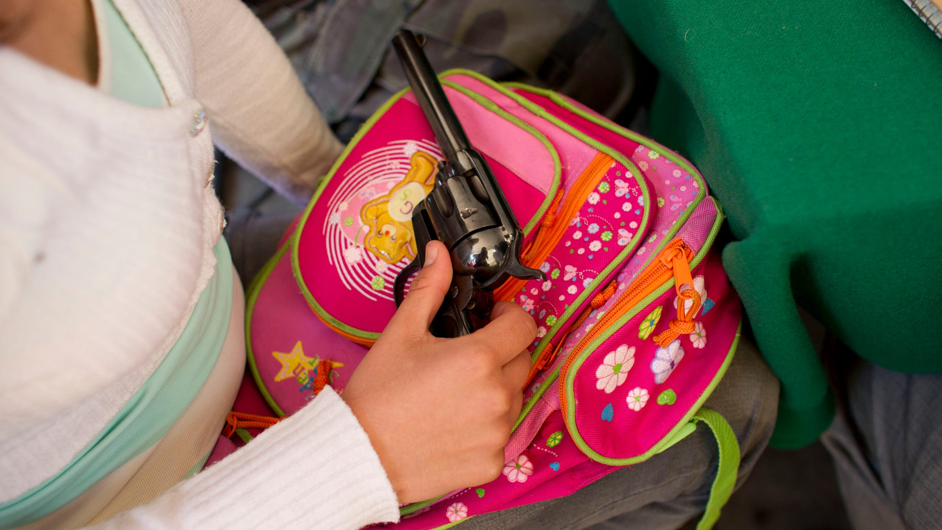 Dec. 24, 2012: A woman holds a revolver before handing it over to city officials during a government program that exchanges people's weapons for bicycles, computers, tablets or money, on Christmas Eve in the Iztapalapa neighborhood of Mexico City.