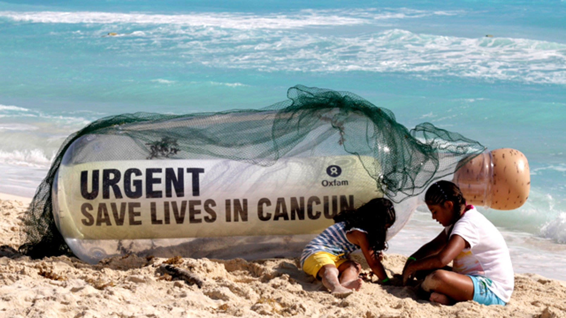 A giant message in a bottle from Oxfam International sits on the beach next to children playing in Cancun, Mexico, Sunday, Nov. 28, 2010. Facing another year without a global deal to curb climate change, the world's nations will spend the next two weeks in Cancun, Mexico, during the annual conference of the 193-nation U.N. climate treaty, debating how to mobilize money to to tackle a changing climate.