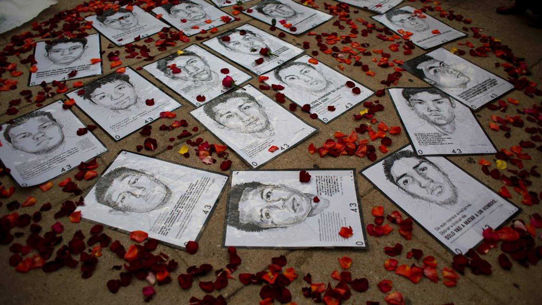 FILE - In this March 26, 2015 file photo, drawings of some of 43 missing rural college students are surrounded by flower petals, forming the shape of a heart, during a protest marking the six-month anniversary of their disappearance, in Mexico City. As millions of Mexicans set up altars to the dead and buy orange flowers to adorn the offerings of food and drink, the parents of 43 students missing since September 2014 are marching, protesting, and seeking other ways to remember their sons, fiercely refusing to accept the government's explanation that they are dead. (AP Photo/Rebecca Blackwell, File)