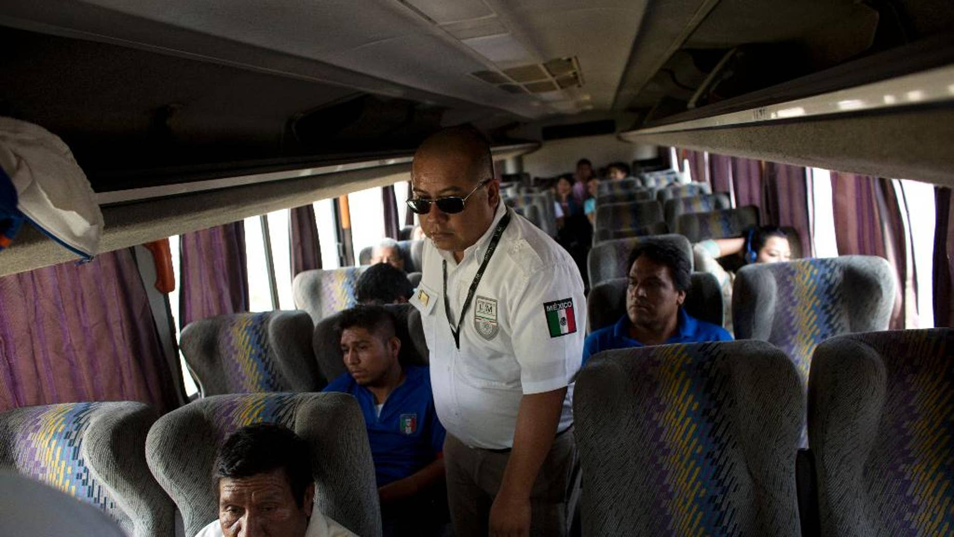 FILE - In this Aug. 27, 2014, file photo, an immigration official checks a bus for Central American migrants, at a roadblock north of Arriaga, Chiapas state, Mexico. According to data from Mexico's National Immigration Institute, Mexico has deported 79 percent more Central Americans in the first four months of 2015 than it did during the same period a year earlier. (AP Photo/Rebecca Blackwell, File)