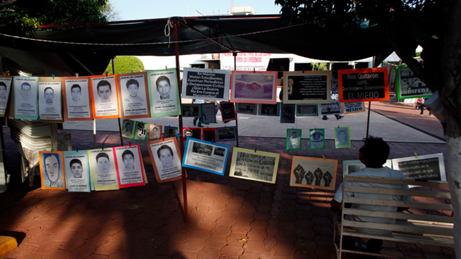 In this Oct. 1, 2015 photo, a man sits next to a permanent installation memorializing the 43 missing students, outside of the municipal palace in the city of Iguala, Mexico. The disappearance of 43 students at the hands of Iguala police on Sept. 26, 2014 began to unveil the scope of police involvement in Mexicos nearly 26,000 recorded disappearances. Amid national outrage over the students abduction, hundreds of families came forward to report their missing relatives, many of them also with the complicity of police. (AP Photo/Dario Lopez-Mills)