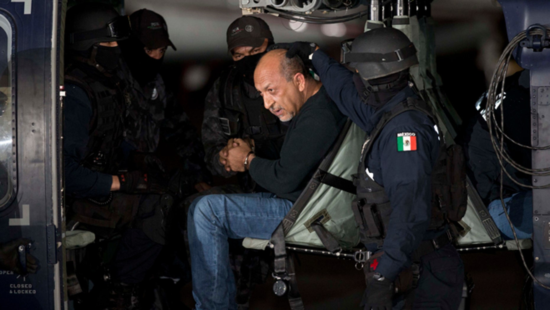 """ADDS PHOTOGRAPHER'S BYLINE - Federal police escort who they identify as Servando """"La Tuta"""" Gomez,""""leader of the Knights Templar cartel, as he sits inside helicopter at the Attorney General's Office hangarin Mexico City, Friday, Feb. 27, 2015.Gomez, a former school teacher who became one of Mexico's most-wanted drug lords as head of the Knights Templar cartel, was captured early Friday by federal police, according to Mexican officials. (AP Photo/Eduardo Verdugo)"""