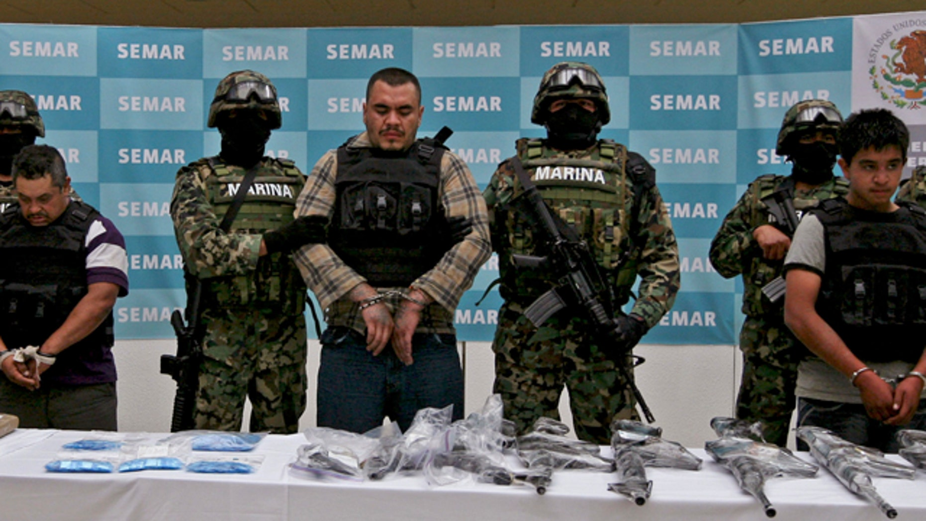 "FILE: Navy members escort Martin Omar Estrada Luna, center, alias ""El Kilo,"" and alleged members of his gang in front of seized weapons and packages containing narcotics during a presentation to the press in Mexico City."