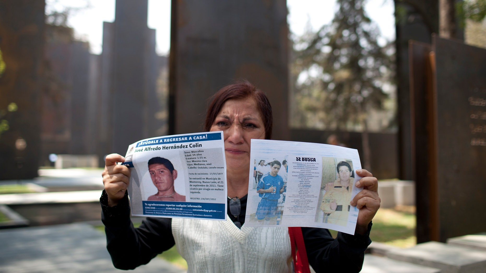 Yolanda Colin, shows leaflets with pictures of her nephew, Jose Alfredo Cilin, who went missing since 2011, as she stands by the new memorial in honor of victims of violence during its unveiling in Mexico City, Friday, April 5, 2013.  The monument to the drug war dead consists of steel panels with nothing but few quotes from famous writers and thinkers. Activists who oppose the monument say the government needs to acknowledge each and every one of those killed. (AP Photo/Alexandre Meneghini)