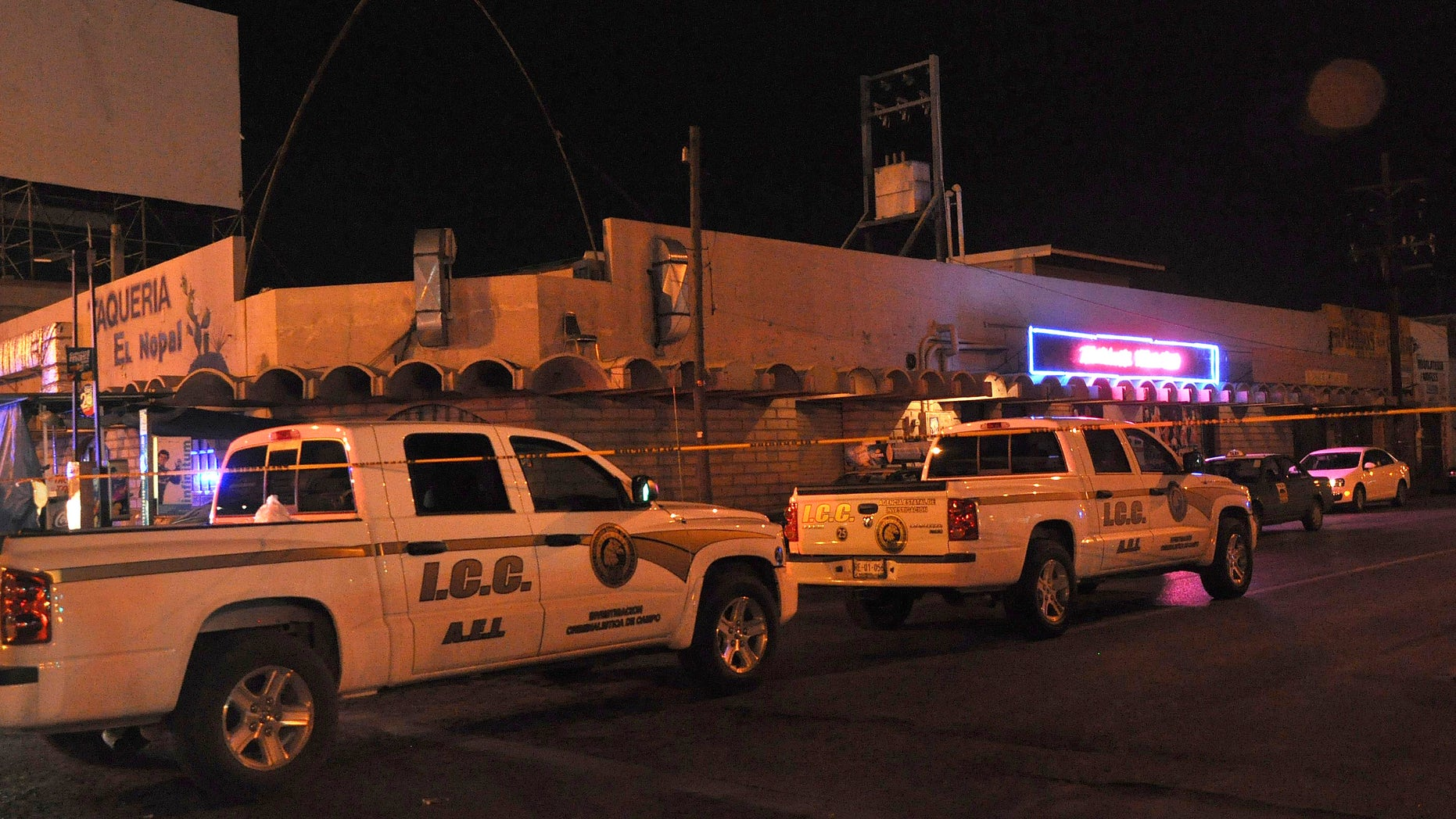 Aug. 14, 2012: Police forensic investigation vehicles sit parked outside Matehuala Men's Club after a shooting inside the night club in Monterrey, Mexico.