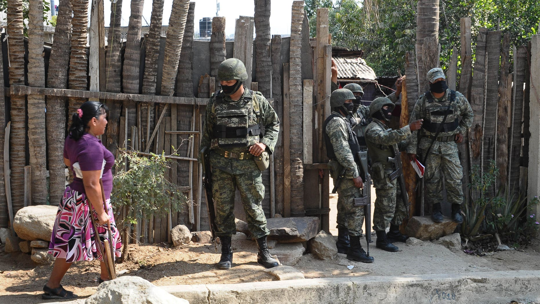 March 15: Mexican army soldiers stand outside a home.  A report based on local research says at least 230,000 have been displaced in Mexico due to drug violence.