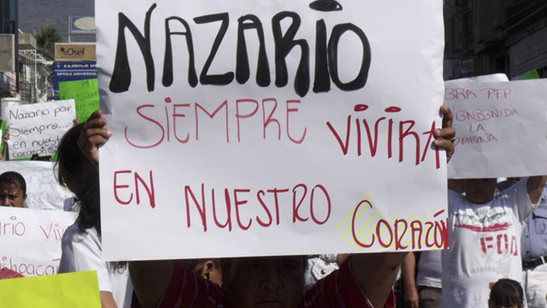 "FILE - In this Dec. 12, 2010 file photo, a man holds a sign that reads in Spanish ""Nazario will always live in our hearts,"" referring to La Familia drug cartel leader Nazario Moreno Gonzalez during a demonstration after the government announced he was killed in Apatzingan, Mexico. Years later on Sunday, March 9, 2014, officials say Moreno was killed in an early morning shootout. (AP Photo/Primera Plana, File)"