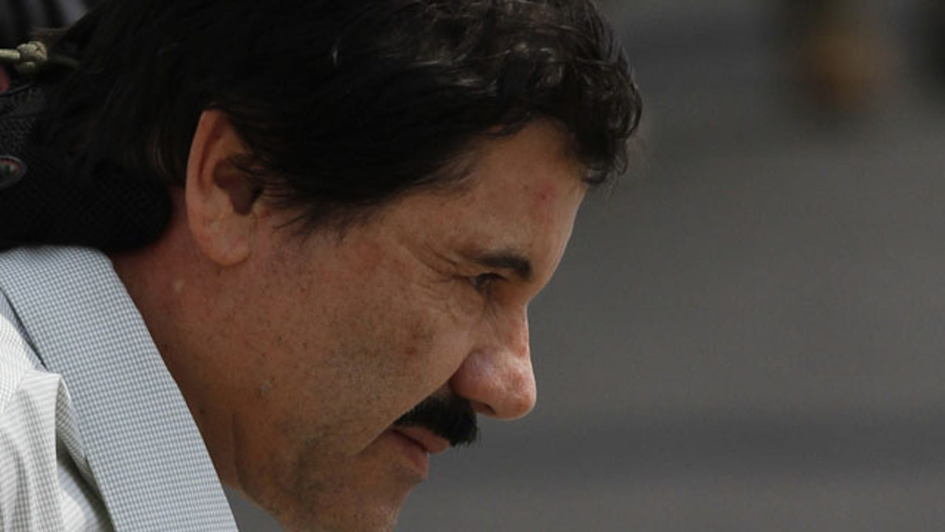 """February 22, 2014: Joaquin """"El Chapo"""" Guzman is escorted to a helicopter in handcuffs by Mexican navy marines at a navy hanger in Mexico City. (AP Photo/Marco Ugarte)"""