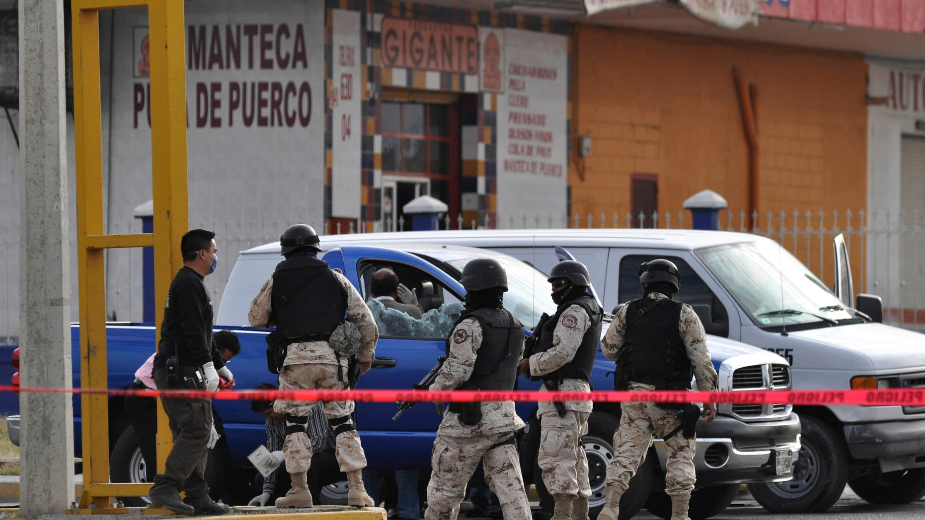 Soldiers patrol as forensics stand next to a truck where two investigative police officers were shot by unidentified assailants in Ciudad Juarez, Mexico, Monday Dec. 6, 2010. One investigative police officer died in the shooting, according to police.