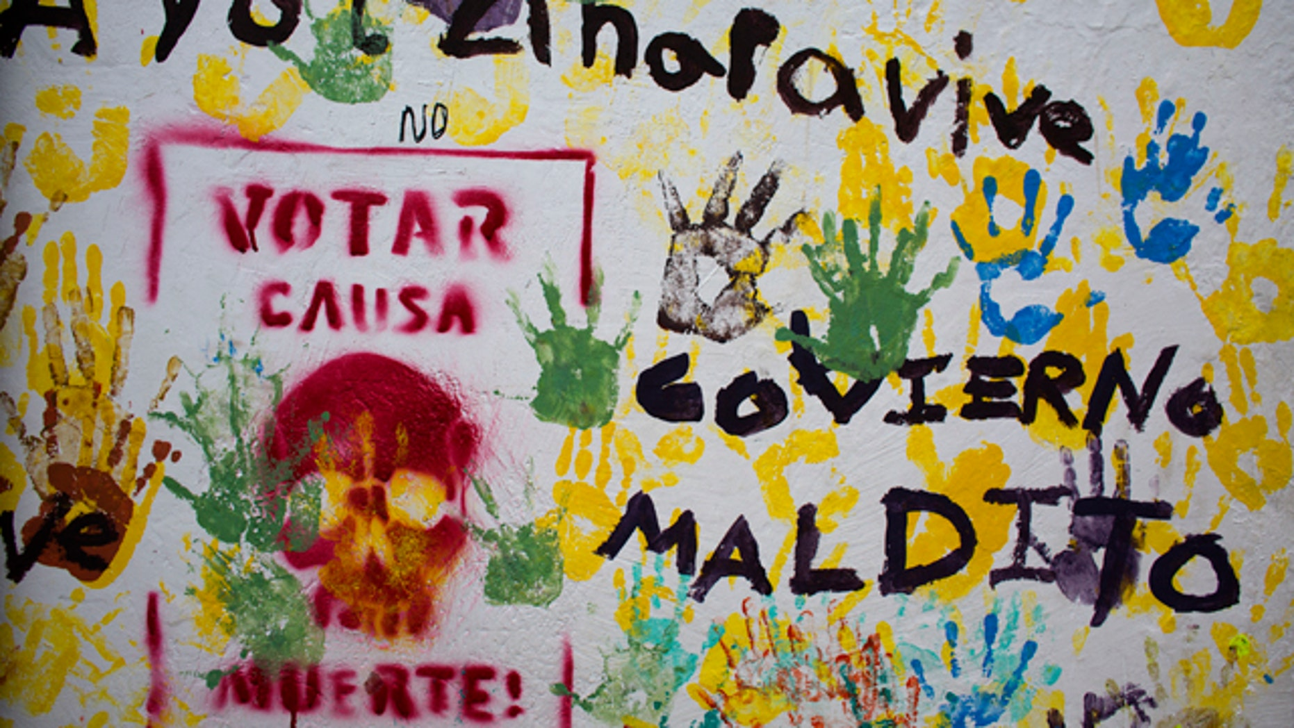"""Graffiti in the central square of Tixtla, home of the rural normal school at Ayotzinapa, reads """"Ayotzinapa lives. Voting causes death. Cursed government,"""" in Tixtla, Mexico, Saturday, June 6, 2015. A day ahead of elections, a community group, many with faces covered by bandanas, stopped all traffic entering and leaving the Guerrero state town of Tixtla along one main road, to search for and burn any campaign or election materials. (AP Photo/Rebecca Blackwell)"""