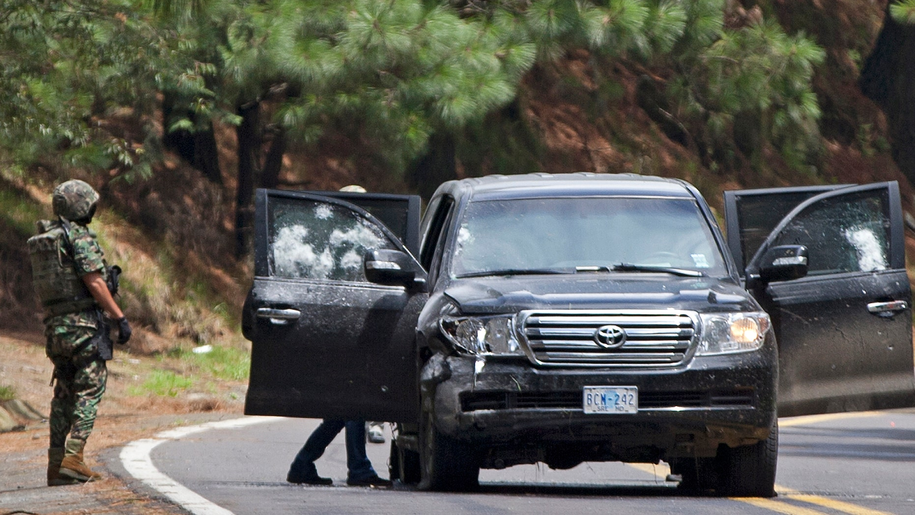 This Aug. 24, 2012, photo shows the armored U.S. embassy vehicle being checked by military personal after it was attacked by unknown assailants on the highway leading to the city of Cuernavaca, Mexico.