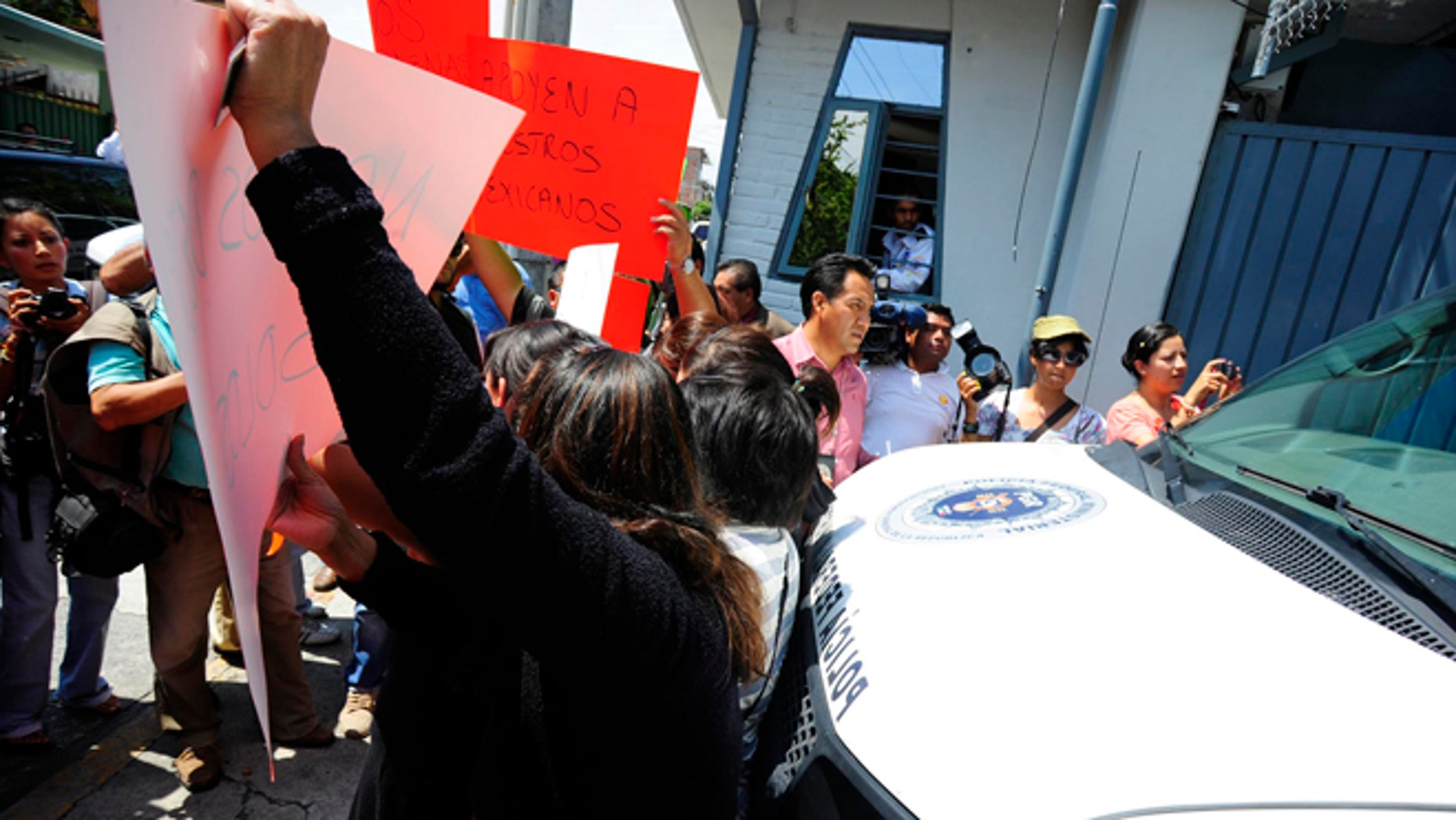 Relatives of the federal policemen involved in last week's shooting against a U.S. embassy vehicle try to block the exit of a van carrying the officers to a federal detention center outside of the Attorney General's office in the city of Cuernavaca, Mexico, Monday Aug. 27, 2012. A judge ruled Monday that the 12 police officers accused of opening fire on a U.S. embassy vehicle and wounding two embassy employees should remain in detention in an incident that has roiled U.S./Mexican relations and drawn fresh attention to serious problems inside Mexico's premier law-enforcement agency. (AP Photo/Tony Rivera)