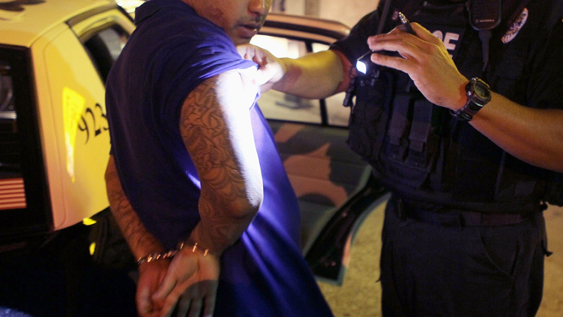 """TUCSON, AZ - JUNE 03:  Leon Gutierrez of the Tucson Police Department's Gang Tactical Unit looks over a suspect's tattoos for signs of gang affiliation following an altercation outside a currency exchange on June 3, 2010 in Tucson, Arizona. The Tucson Police Department is currently gearing up to begin training its officers on the implementation of the state's controversial new immigration law SB 1070. Among other things the new law makes it a state crime to be an """"unauthorized alien"""" or to knowingly harbor, hire or transport an unauthorized alien. A Tucson police officer was one of the first to file suit in federal court challenging the new law.  (Photo by Scott Olson/Getty Images)"""