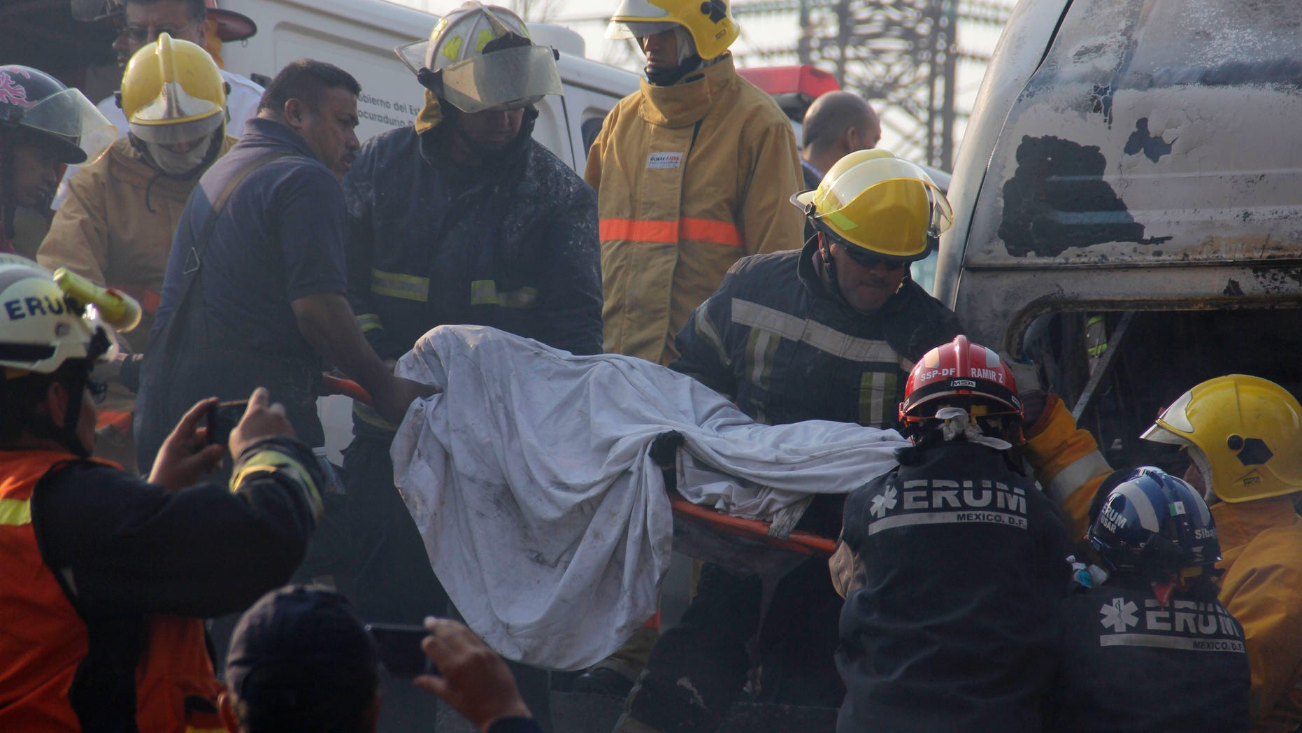 May 7, 2013: Firefighters remove a body from a destroyed home after a gas tanker truck exploded on a nearby highway in the Mexico City suburb of Ecatepec early Tuesday.