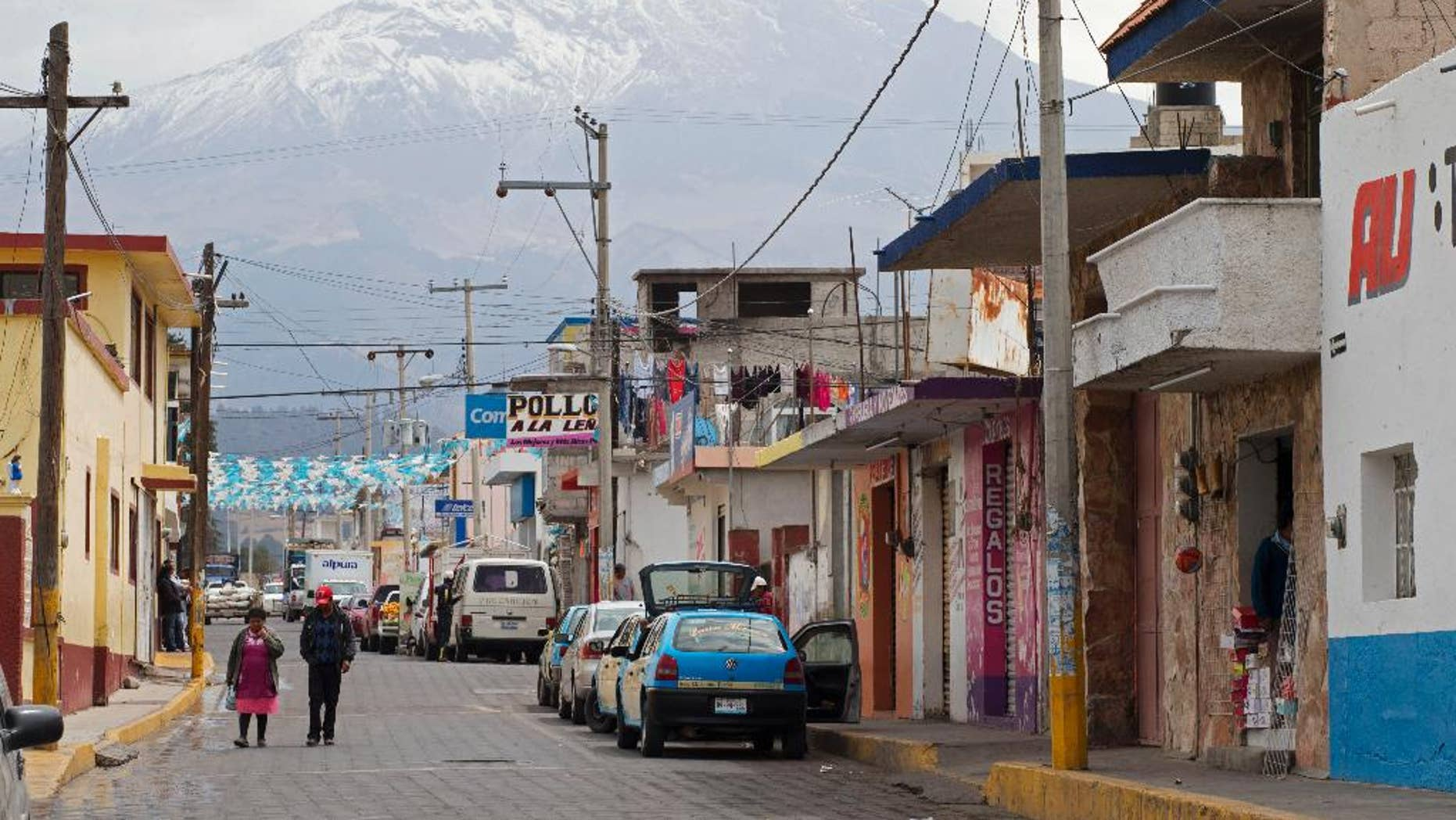 FILE - In this March 10, 2015 file photo, the Pico de Orizaba volcano rises above the town of Tlachichuca in Mexico's Puebla state. Mountaineers discovered another mummified body on Mexico's tallest peak and brought it down on Thursday, June 4, 2015, making it the third body found in recent months. The body's identity was still being confirmed. (AP Photo/Rebecca Blackwell, File)