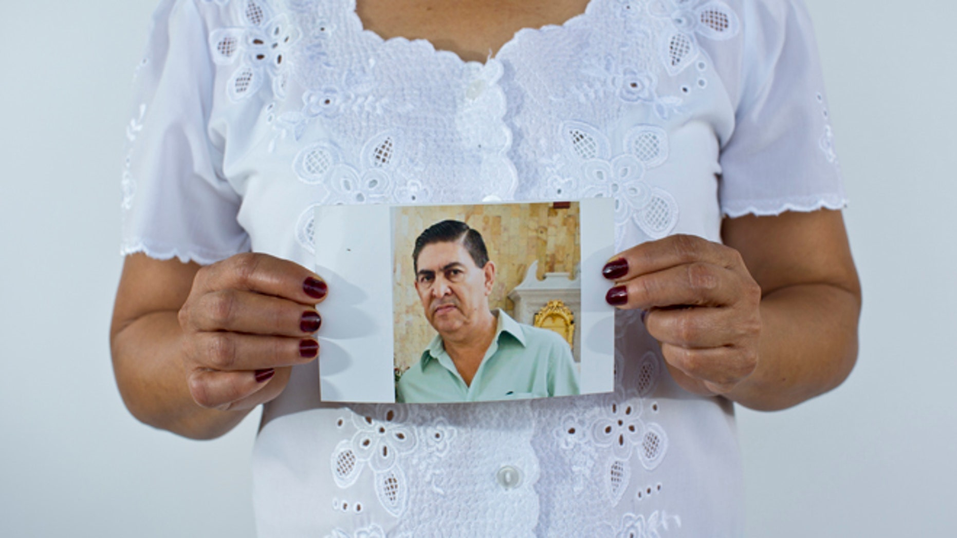In this June 2, 2015 photo, Yolanda Alvarez Antúnez holds up an image of her husband, Luis Alberto Ramiíez Castillo, in Iguala, Mexico. Her husband was 54 years old when he was kidnapped by armed men outside of his home on Jan. 10, 2013. While trying to pay for the ransom, Yolanda herself was taken by the kidnappers and had to pay extra to be freed. (AP Photo/Dario Lopez-Mills)