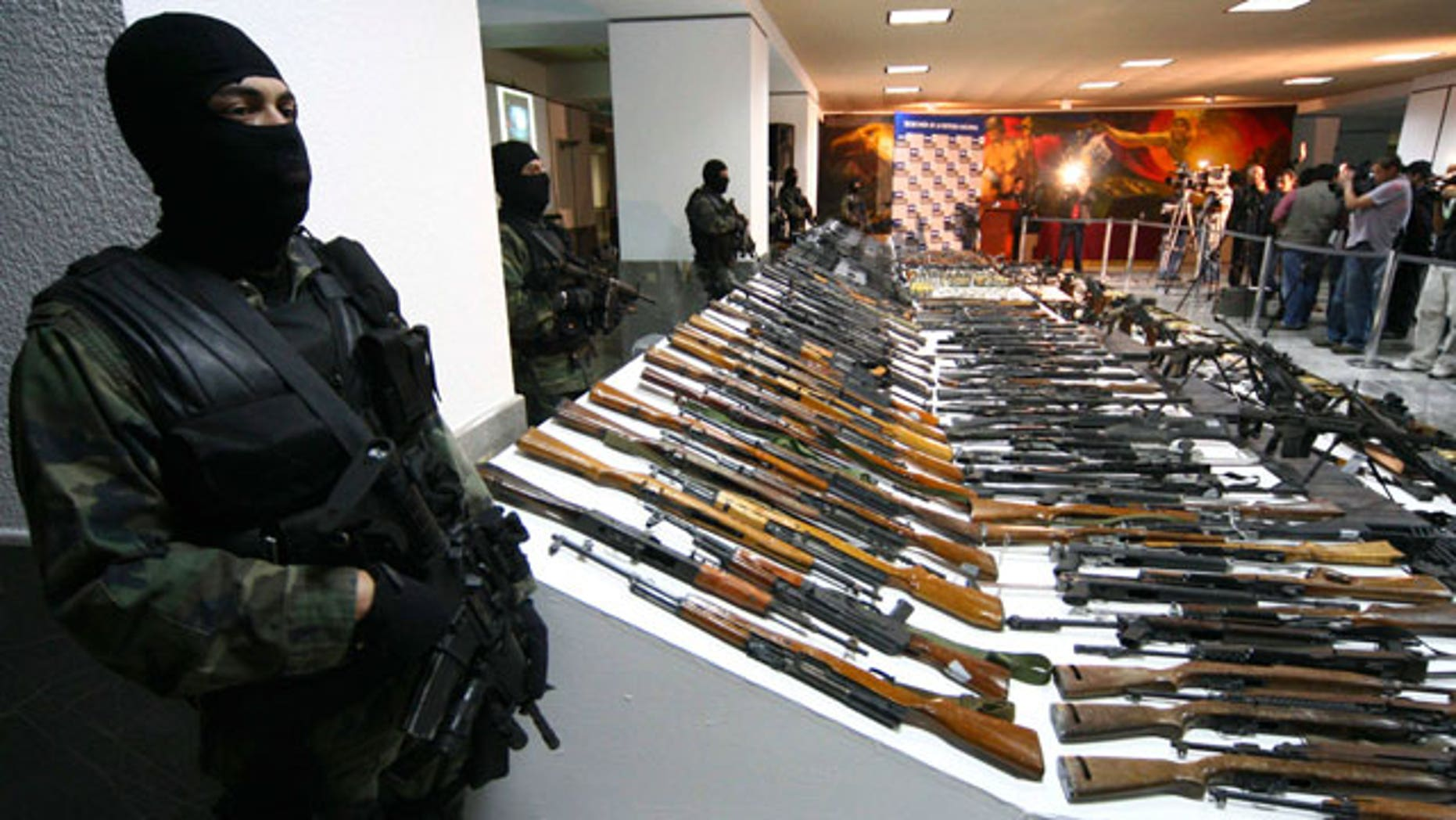 FILE: Soldiers stand guard near seized weapons during a news conference at the Defense Headquarters in Mexico City.