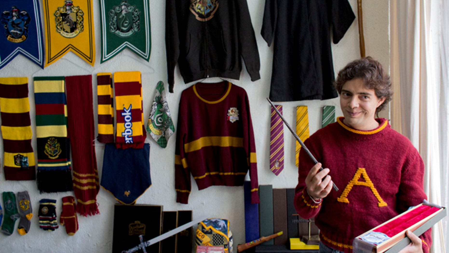 Menahem Asher Silva Vargas a 37 year old lawyer, displays a favorite wand, as he shows off his collection of Harry Potter memorabilia after being awarded the Guinness World Record title for the largest collection, in Mexico City, Monday, Sept. 29, 2014. Silva's collection consists of more than 3000 individual items, including figurines, trading cards, wands, clothing, and accessories.(AP Photo/Rebecca Blackwell)
