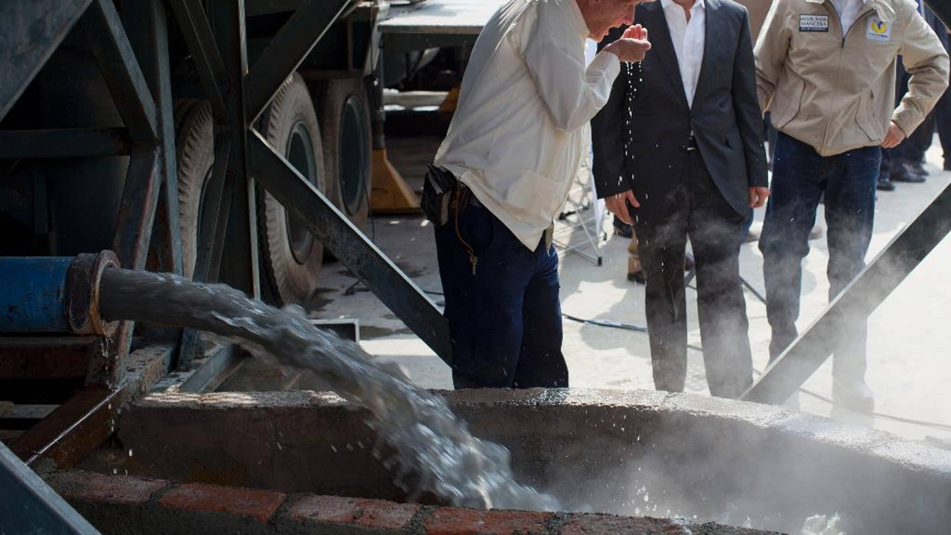 FILE - In this Jan. 23, 2013 file photo, National Water Commission David Korenfeld, center right, watches geologist Federico Mooser take a drink of water from an exploratory well where an aquifer was discovered, in Mexico City. Korenfeld announced his resignation Thursday, April 9, 2015, a week after social media filled with photographs, apparently taken by a neighbor on March 29, showing people walking with suitcases to a helicopter marked with the agency's name. (AP Photo/Dario Lopez-Mills, File)