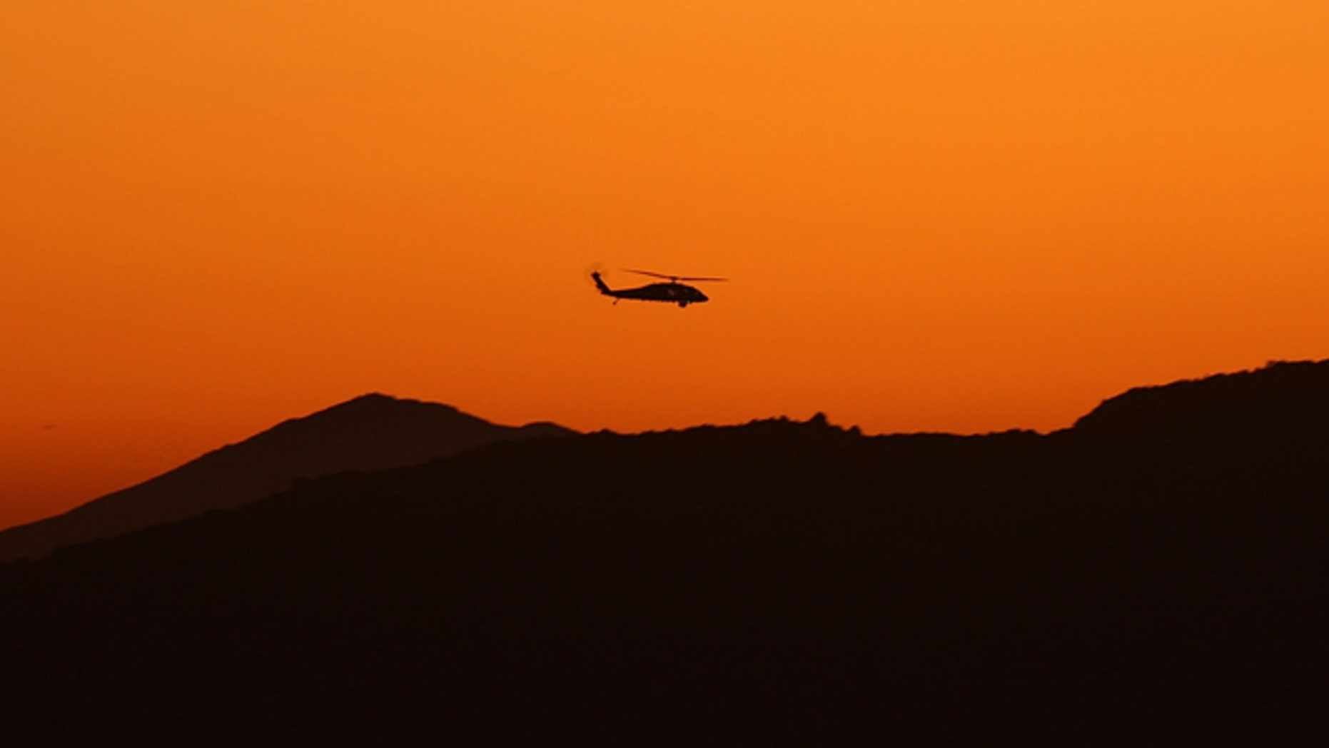 CAMPO, CA - JULY 29:  A helicopter patrols the hills where US Border Patrol agents are carrying out special operations following the first fatal shooting of a US Border Patrol agent in more than a decade on July 29, 2009 near the rural town of Campo, some 60 miles east of San Diego, California. 30-year-old agent Robert Rosas was killed on July 23 when he tracked a suspicious group of people alone in remote brushy hills north of the border in this region. Violence has been escalating in Mexico with fights between well-armed drug cartels and the army becoming common since Mexican President Felipe Calderon began his army-backed war on the cartels. Since the conflict began in late 2006, 12,800 people have been killed. Mexican officials charge that guns which are easily smuggled in from the US have flooded into Mexico where gun laws are strict.   (Photo by David McNew/Getty Images)