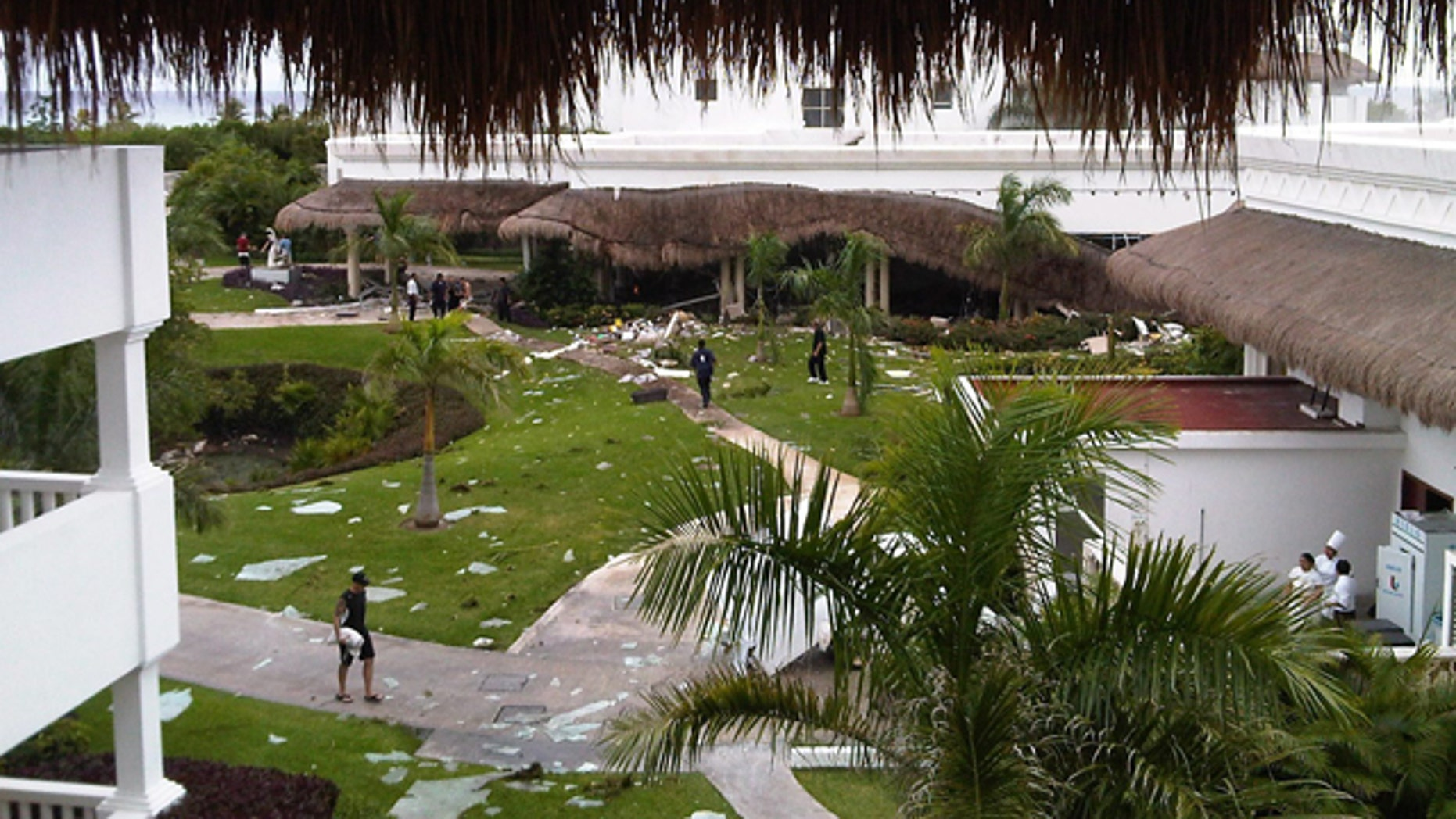 In this photo released by 570 News via The Canadian Press, debris is seen scattered on the lawn of a resort hotel in Playa del Carmen, Mexico, Sunday Nov. 14, 2010.  According to the Attorney General of the state of Quintana Roo, Francisco Alor, a blast at the hotel on Mexico's Caribbean coast, apparently caused by an accumulation of gas, has killed six people and left 15 wounded. (AP Photo/Pete Travers, 570 News via The Canadian Press)