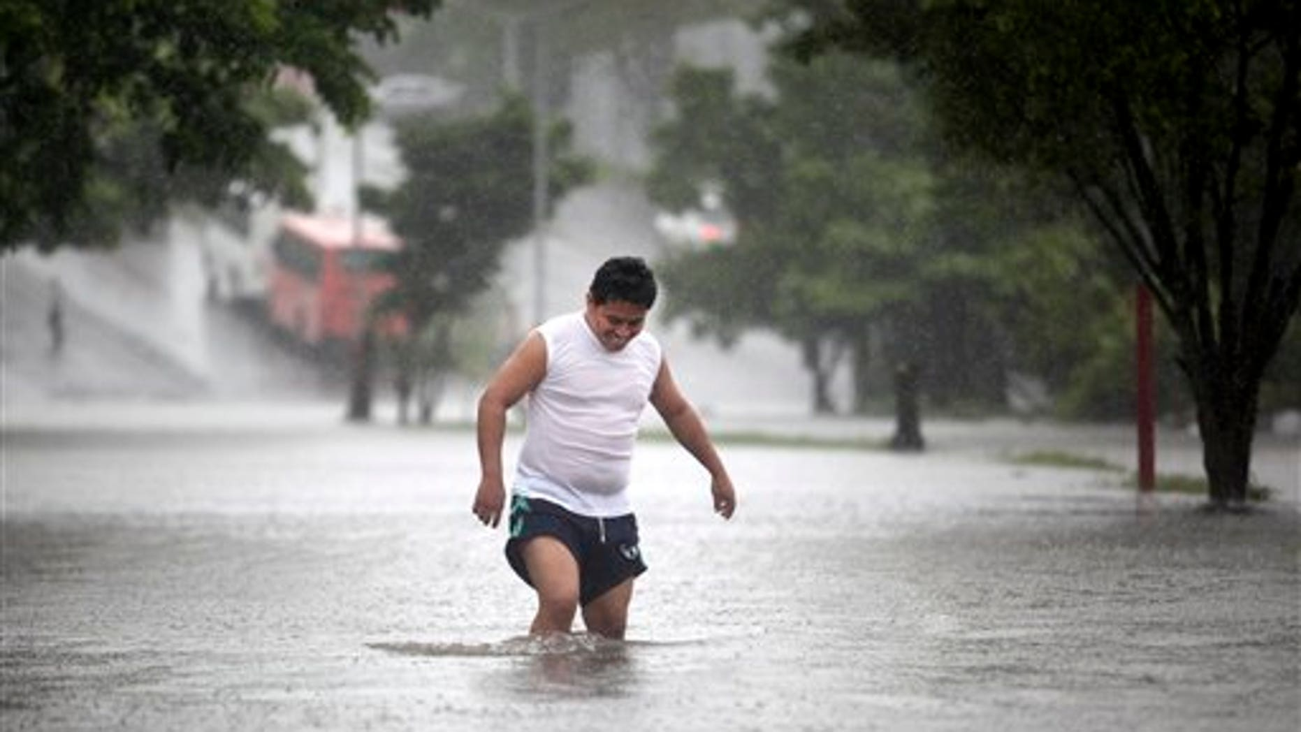 A man walks through a flooded street during heavy rains caused by Tropical Storm Ingrid in the Gulf port city of Veracruz, Mexico, Friday Sept. 13., 2013. (AP Photo/Felix Marquez)