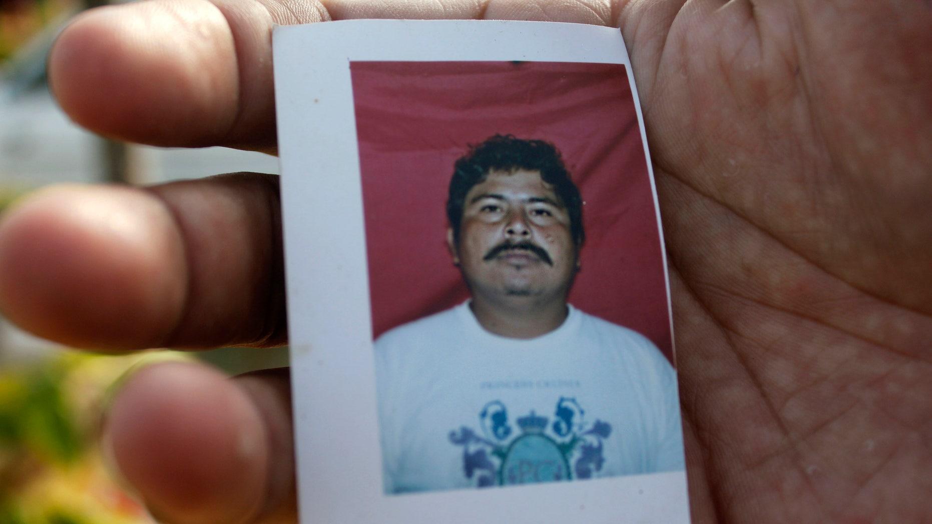 A relative of journalist Gregorio Jimenez holds a photo of him in Coatzacoalcos, Mexico.