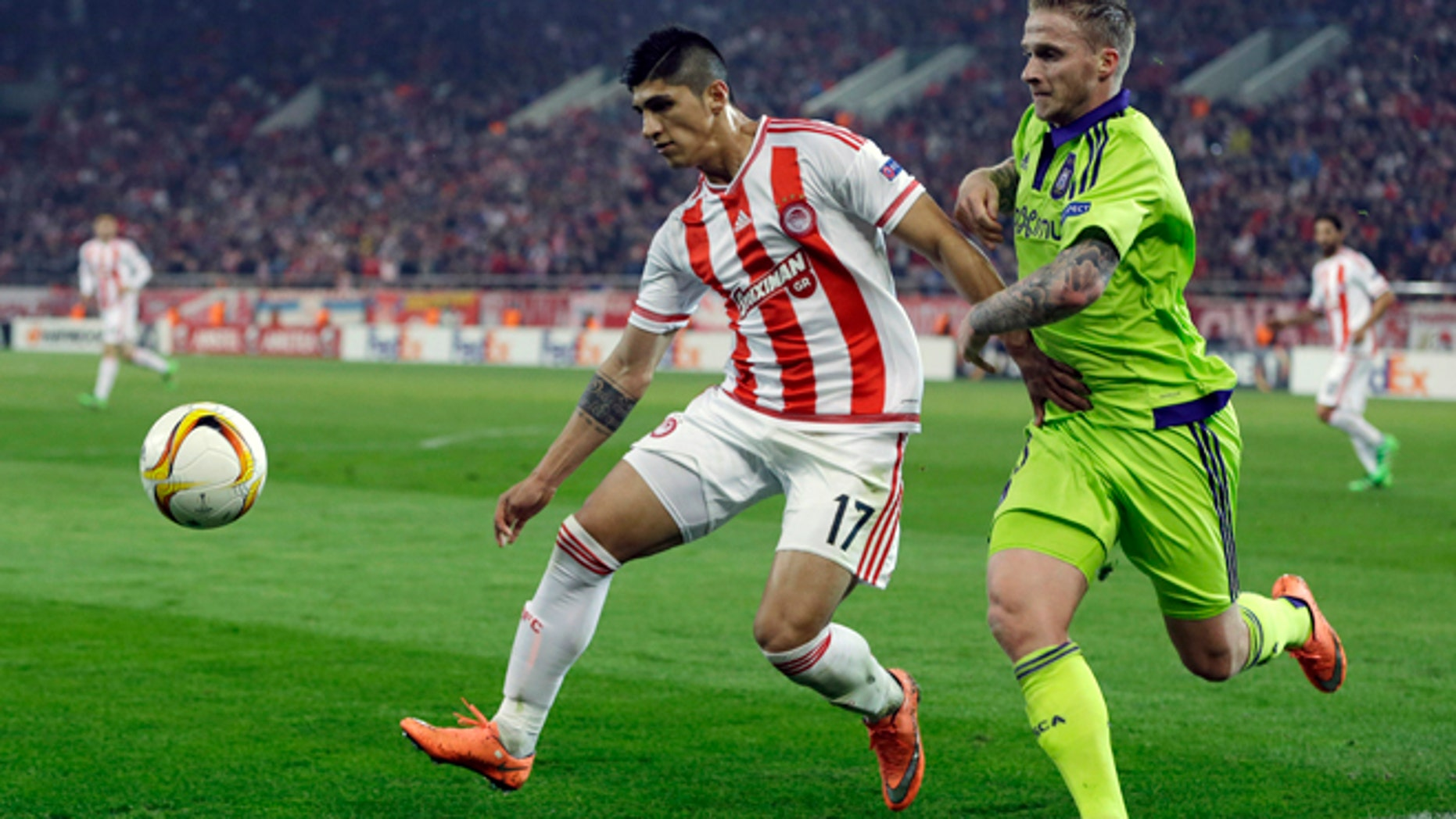 FILE - In this Thursday, Feb. 25, 2016 file photo, Olympiakos' Alan Pulido, left, fights for the ball with Anderlecht's Alexander Buttner during the Europa League round of 32 soccer match at the Georgios Karaiskakis stadium in the port of Piraeus, near Athens. A state official says that Mexican soccer star Alan Pulido has been kidnapped in the northern border state of Tamaulipas. Pulido is a forward for the Greek team Olympiacos and has made several appearances for Mexicos national team, though he wasnt called up for the upcoming Copa America tournament. The official says the 25-year-old player was kidnapped near his hometown of Ciudad Victoria on Sunday, May 29, 2016 after leaving a party. (AP Photo/Thanassis Stavrakis, file)