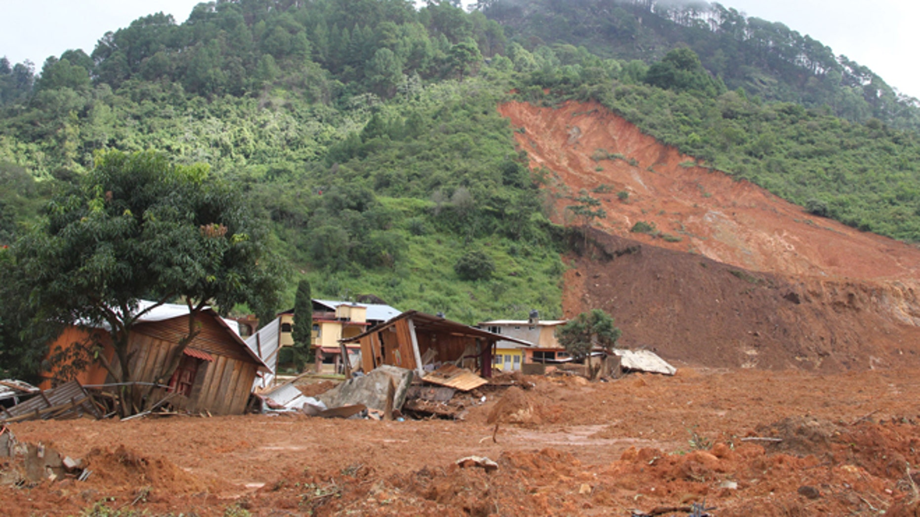 In this photo released by Mexico's Secretary of the Interior, structures lay in ruins at the site of a landslide in the village of La Pintada, Mexico, Thursday, Sept. 19, 2013. La Pintada was was affected by the twin paths of Tropical Storm Manuel and Hurricane Ingrid, which simultaneously pounded both of Mexico's coasts over the weekend, triggering floods and landslides across coastal and inland areas. (AP Photo/Mexico's Secretary of the Interior)