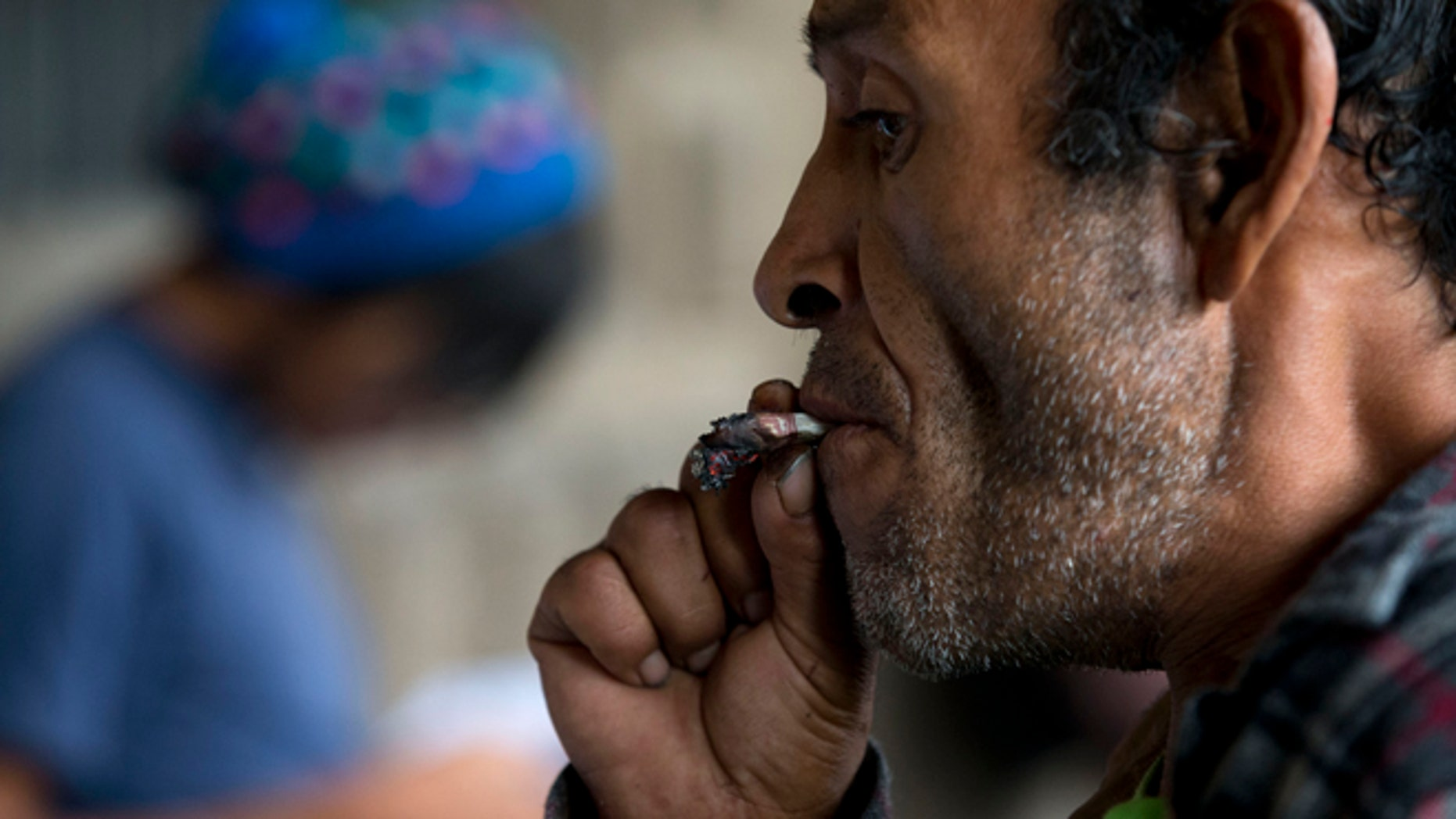 A passerby stops to bum a smoke from marijuana legalization activists, outside Mexico's Supreme Court which was scheduled to discuss a case challenging the constitutionality of a ban on recreational use in Mexico City, Wednesday, Oct. 28, 2015. The court postponed for at least one week the planned debate, which could open the way for Mexicans to grow and smoke marijuana recreationally. (AP Photo/Rebecca Blackwell)