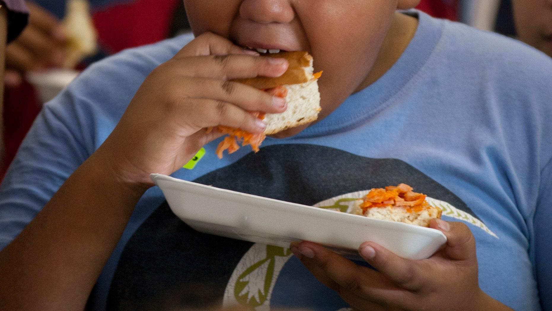 "A boy eats a piece of a ""mega torta"" sandwich during a Torta Festival in a plaza Mexico City, Wednesday, Aug. 1, 2012. Cooks prepared the 52 meter sandwich during the festival in an attempt to assemble the largest torta in Mexico's history. (AP Photo/Eduardo Verdugo)"