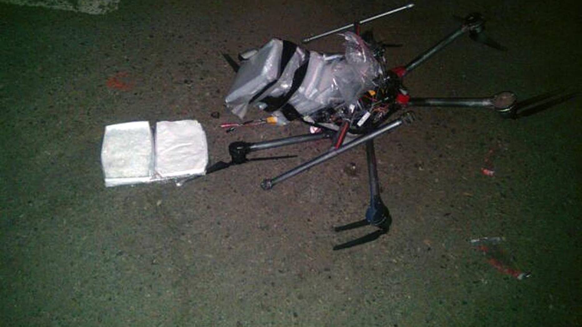 In this image released by the Tijuana Municipal Police on Wednesday Jan. 21, 2015, a drone loaded with packages containing methamphetamine lies on the ground after it crashed into a supermarket parking lot in the city of Tijuana on Tuesday Jan. 20, 2015. According to police, six packets of the drug, weighing more than six pounds, were taped to the six-propeller remote-controlled aircraft. Authorities are investigating where the flight originated and who was controlling it. He said it was not the first time they had seen drones used for smuggling drugs across the border. Other innovative efforts have included catapults, ultralight aircraft and tunnels. (AP Photo/Secretaria de Seguridad Pública Municipal de Tijuana)