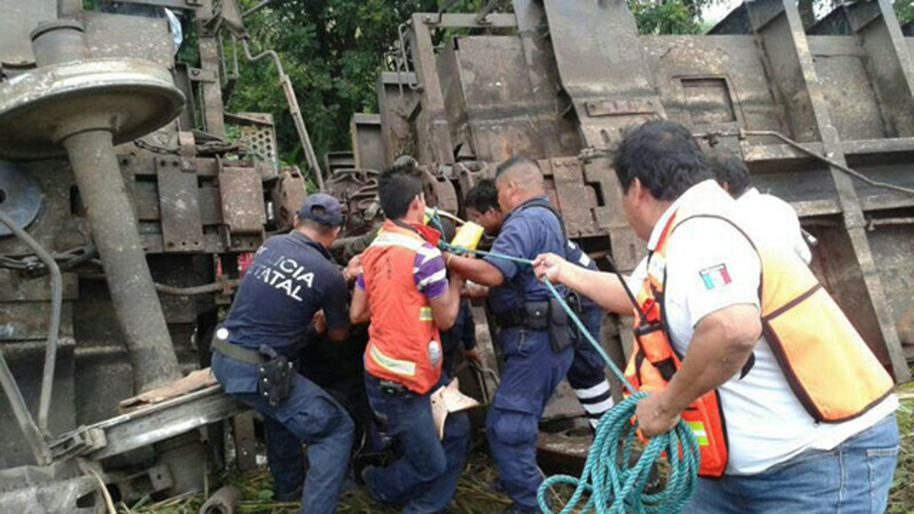 August 25, 2013: In this photo release by the Civil Protection of the State of Tabasco, police agents and rescue workers work at a site where a train derailed in Tabasco, Mexico. (AP Photo)