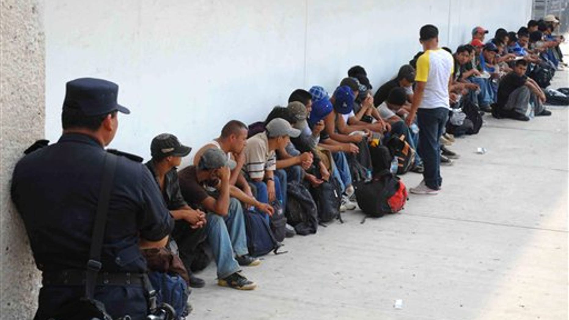 Migrants who were found in two trailer trucks bound for the United States, sit under the guard of a policeman in Tuxtla Gutierrez, Mexico, Tuesday May 17, 2011.  Chiapas authorities say they rescued 513 migrants: 410 of the migrants were from Guatemala, 47 from El Salvador, 32 from Ecuador, 12 from India, six from Nepal, three from China and one each from Japan, the Dominican Republic and Honduras. (AP Photo/Alejandro Estrada)