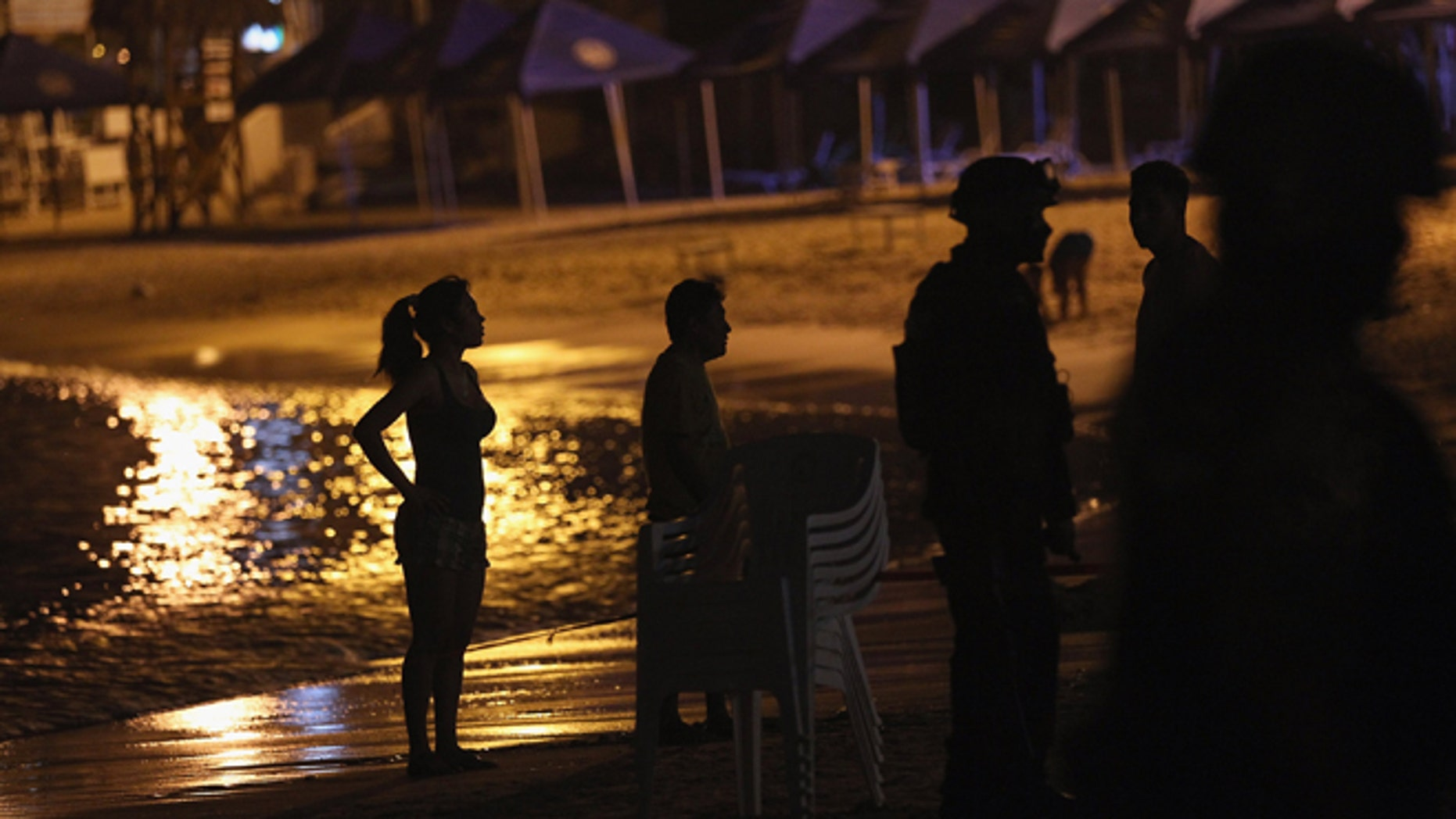 ACAPULCO, MEXICO - MARCH 04:  Mexican tourists and soldiers stand look on at the site of a suspected drug-related execution on Acapulco's famous Caleta Beach on March 4, 2012 in Acapulco, Mexico. Drug violence has surged in the coastal resort in the last year, making Acapulco the second most deadly city in Mexico after Juarez. One of Mexico's top tourist destinations, Acapulco has suffered a drop in business, especially from foreign tourists, due to the violence. Toursim accounts for about 70 percent of the economy of Acapulco's state of Guerrero and 9 percent of Mexico's economy.  (Photo by John Moore/Getty Images)