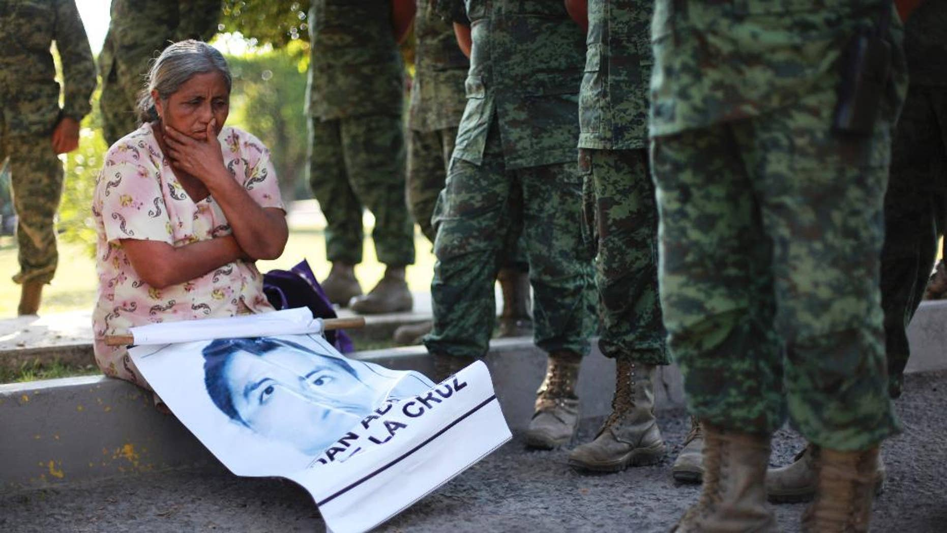 FILE - In this Dec. 18, 2014 file photo, the mother of missing college student Adan Abarajan de la Cruz sits at the foot of soldiers outside a military base during a protest by the families of 43 missing students over the army's alleged responsibility or lack of response to the students' disappearance in Iguala, Mexico. A group of independent experts said Monday, Aug. 17 2015, that Mexican authorities withheld information from family members of 43 college students who disappeared after a confrontation with police, not notifying them that some of the young men's clothing was discovered shortly after they went missing. (AP Photo/Felix Marquez, File)
