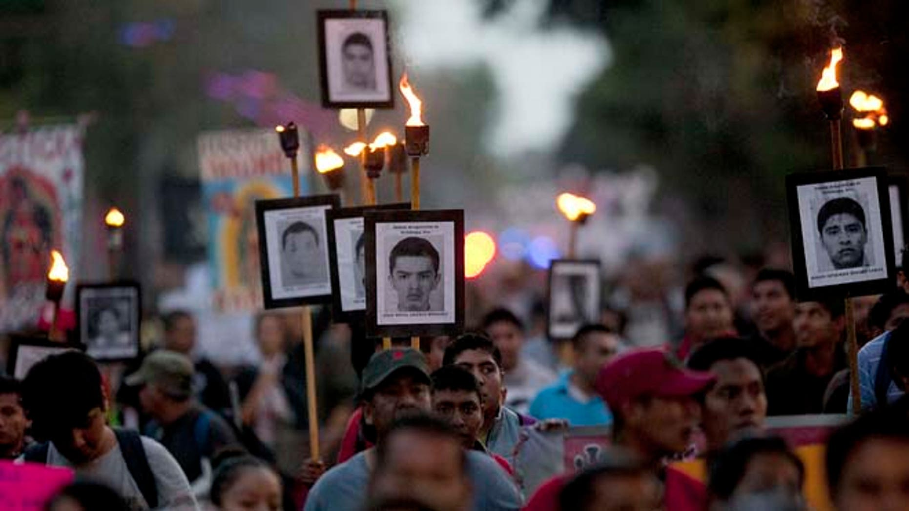 FILE - In this Dec. 26, 2015, file photo, relatives of the 43 missing students from the Isidro Burgos rural teachers college march holding pictures of their missing loved ones during a protest in Mexico City. An appeals court ruling is threatening to derail Mexicoâs effort to prosecute suspects in one of its most notorious crimes of recent years: the disappearance and presumed murder of the 43 students in Guerrero state. (AP Photo/Marco Ugarte, File)