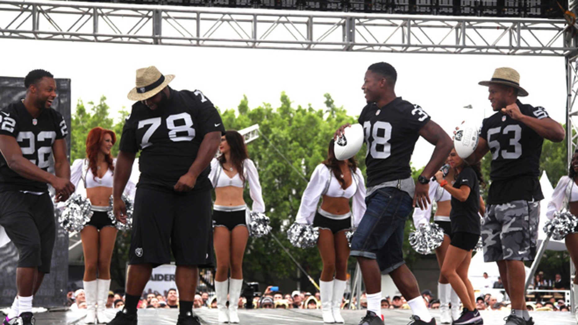 Oakland Raiders players, from left, Taiwan Jones (22), Justin Ellis (78), T.J. Carrie (38) and Malcolm Smith (53) dance before fans at Azteca Stadium where the team announced their third day NFL picks in Mexico City, Saturday, April 30, 2016. The Raiders will play the Houston Texans at Azteca on Nov. 21, 2016 during the NFL regular season. (AP Photo/Marco Ugarte)