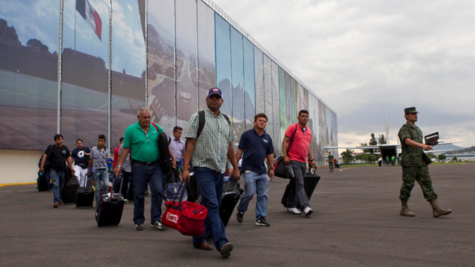 Mexican and foreign tourists arrive at an Air Force hangar in Mexico City after being airlifted out of the hurricane-ravaged resort area of Los Cabos by the Mexican armed forces, in Mexico City, Tuesday, Sept. 16, 2014. Travelers are being flown free of charge to airports in Tijuana, Mazatlan, Guadalajara and Mexico City to catch connecting flights and, in the case of foreigners, receive consular assistance. (AP Photo/Christian Palma)