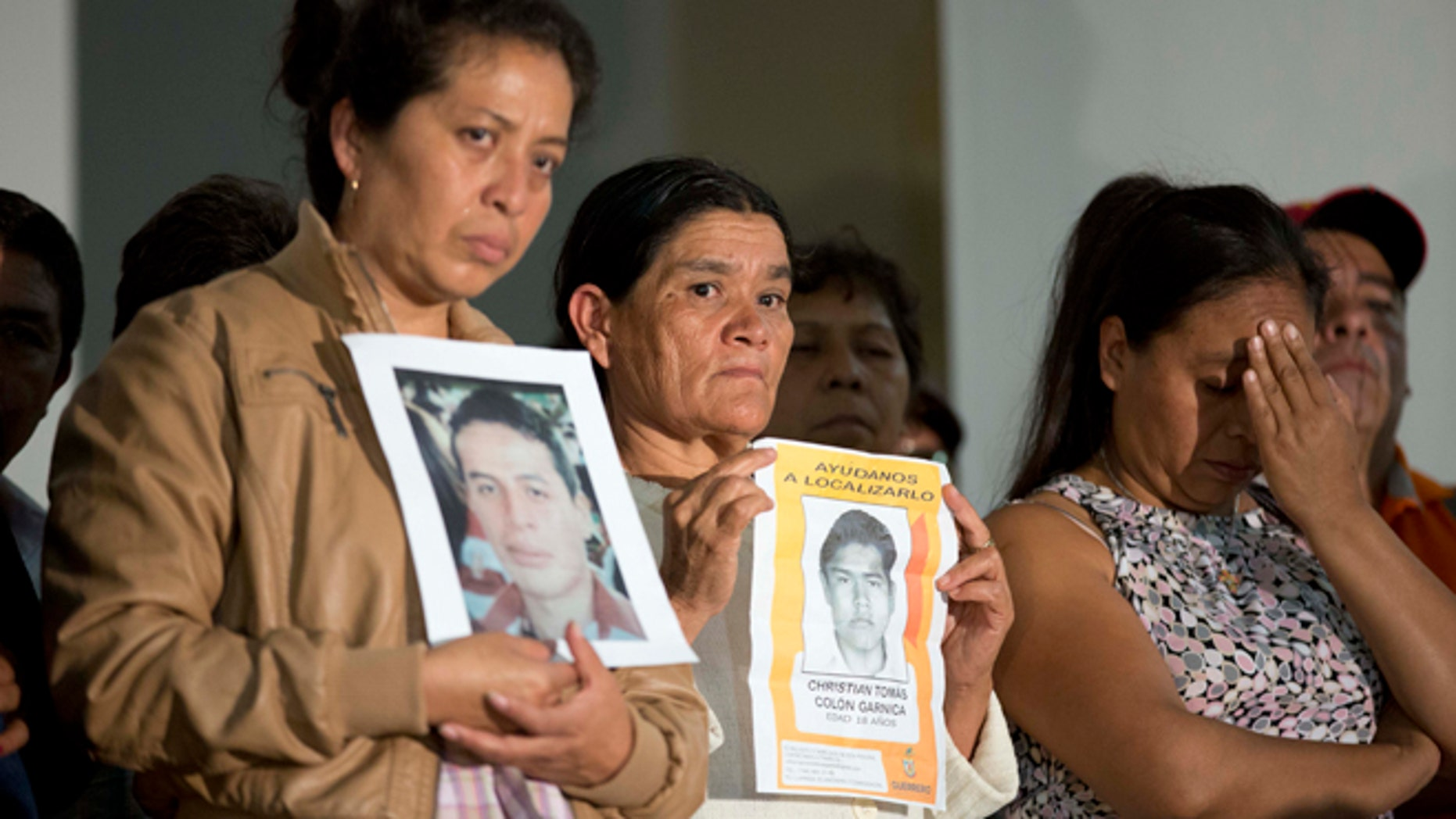 Parents of missing students holding pictures of the missing, attend the press conference after a meeting with Mexico's President Enrique Pena Nieto in  Mexico, City, Wednesday Oct. 29, 2014. President Enrique Pena Nieto met with parents of 43 teachers college students Wednesday for the first time since they disappeared over a month ago, when investigators say police detained the students and handed them over to a drug gang. (AP Photo/Eduardo Verdugo)