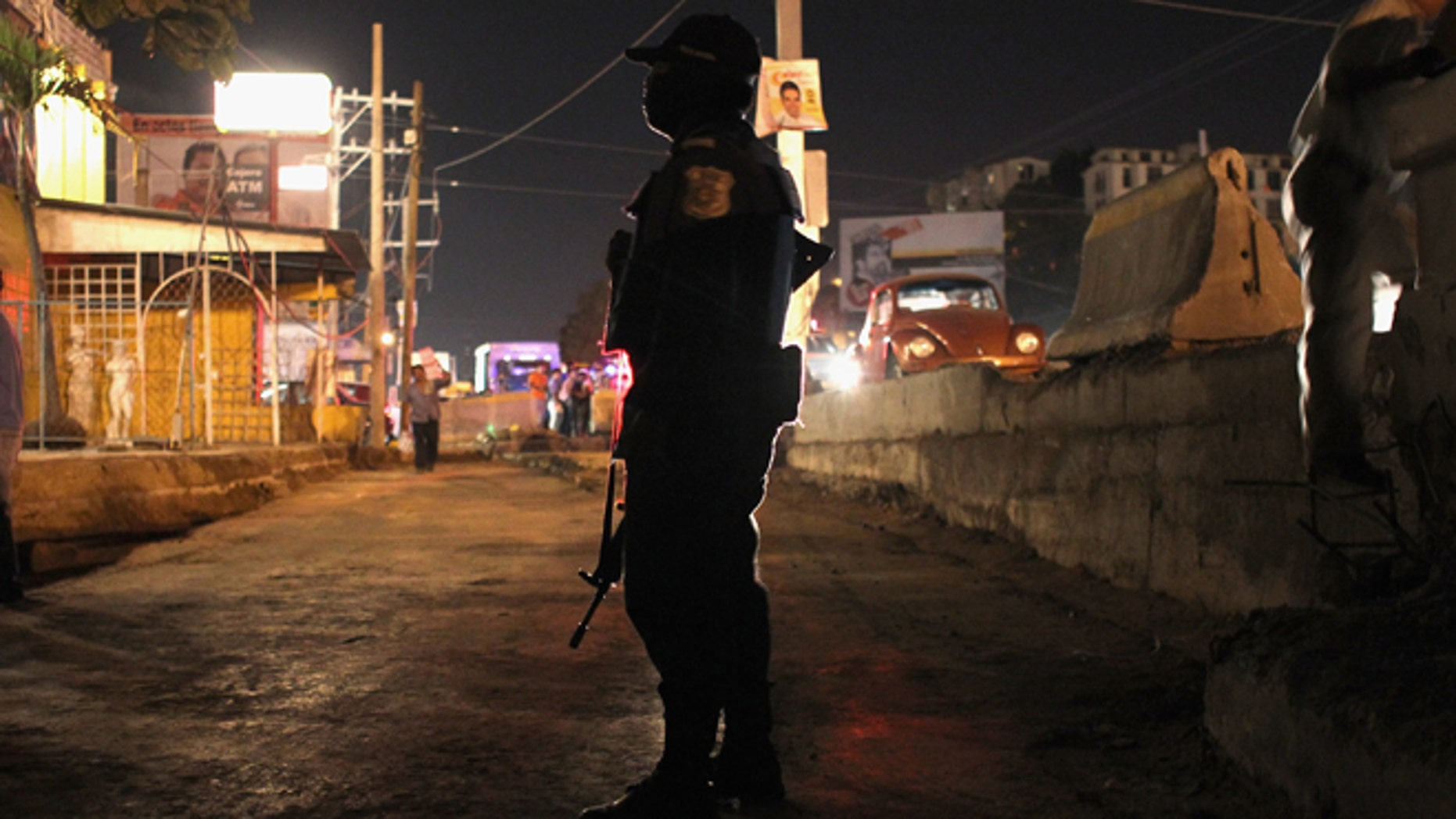 A federal policeman stands guard at the scene of a suspected drug-related execution on March 1, 2012 in Acapulco, Mexico. (Photo by John Moore/Getty Images)