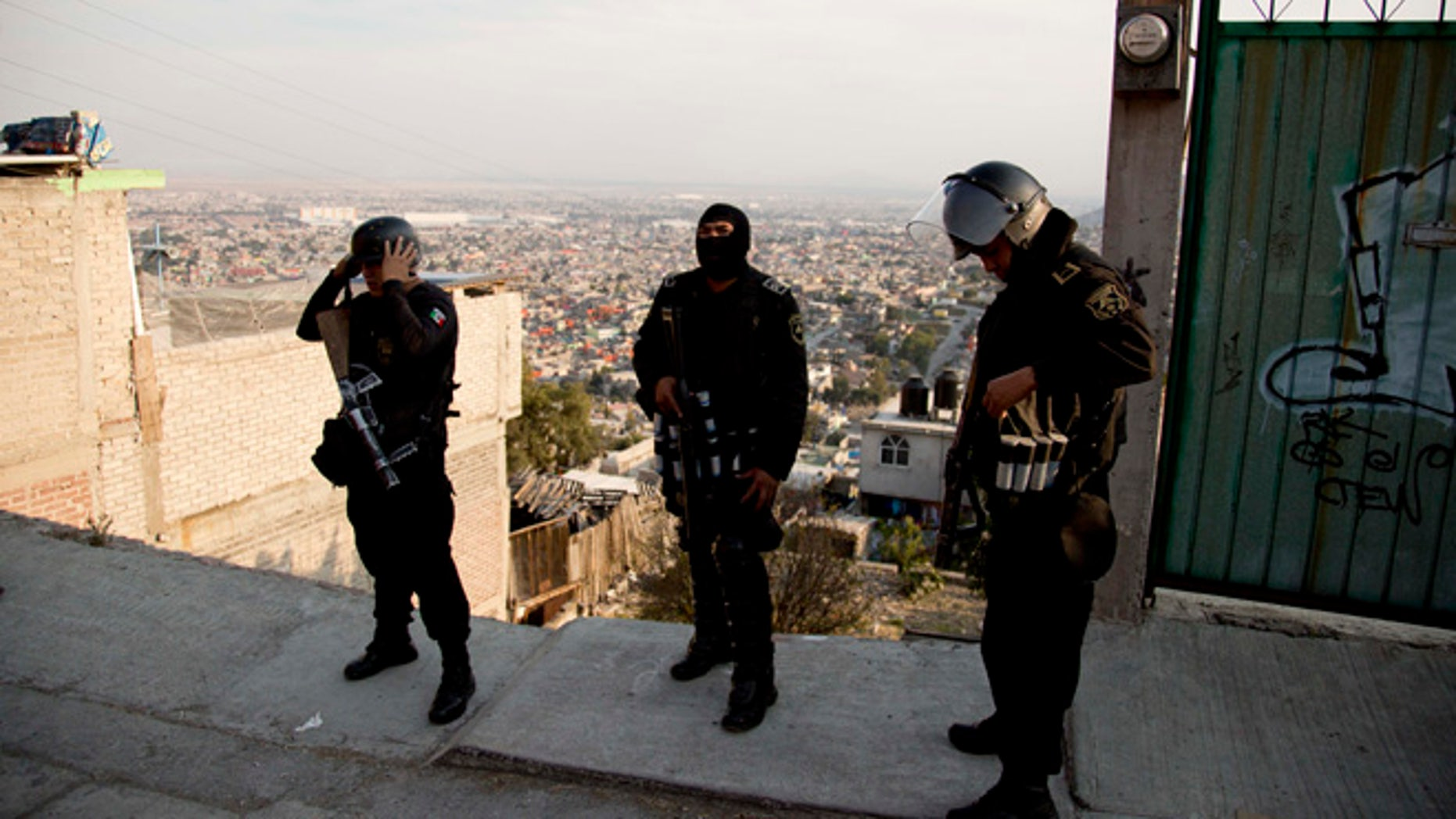 In this Jan. 19, 2015 photo, police officers prepare for an security operation in Ecatepec, a rough neighborhood on the outskirts of Mexico City. Pope Francis will hold the largest public event of his visit to Mexico when he celebrates Mass on an outdoor esplanade in Ecatepec on Feb. 14, 2016. (AP Photo/Eduardo Verdugo)