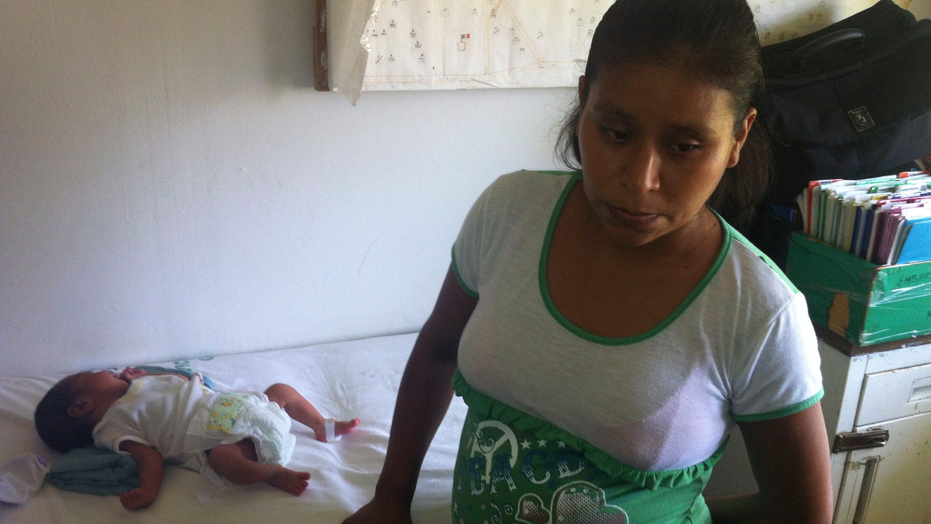 In this photo, 29-year-old Irma Lopez stands next to her newborn son Salvador at a clinic in the town of Jalapa de Diaz, Mexico. Mexico officials have suspended a health center director after Lopez, an indigenous woman, was denied entry to his clinic and was forced to give birth on the lawn.