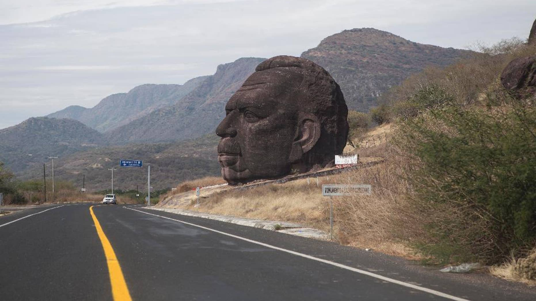 In this Tuesday, Dec. 23, 2014 photo, a monument in honor of Mexico's former President Lazaro Cardenas stands along a highway between Arcelia and Ciudad Altamirano on the state border of Guerrero and Michoacan, Mexico. The bishop of the diocese in Ciudad Altamirano said Friday, Dec. 26 that the Rev. Gregorio Lopez Gorostieta was found dead with a gunshot wound to the head, near this statue, on Christmas Day. Gorostieta disappeared on Monday from the seminary in the city where he taught. (AP Photo/Christian Palma)